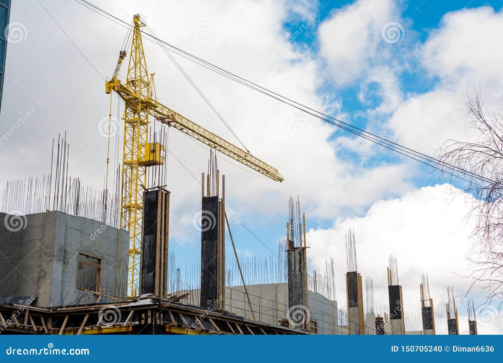 Il processo di costruzione dell edificio residenziale multipiano, una gru a torre gialla, ha versato le colonne concrete con i mo