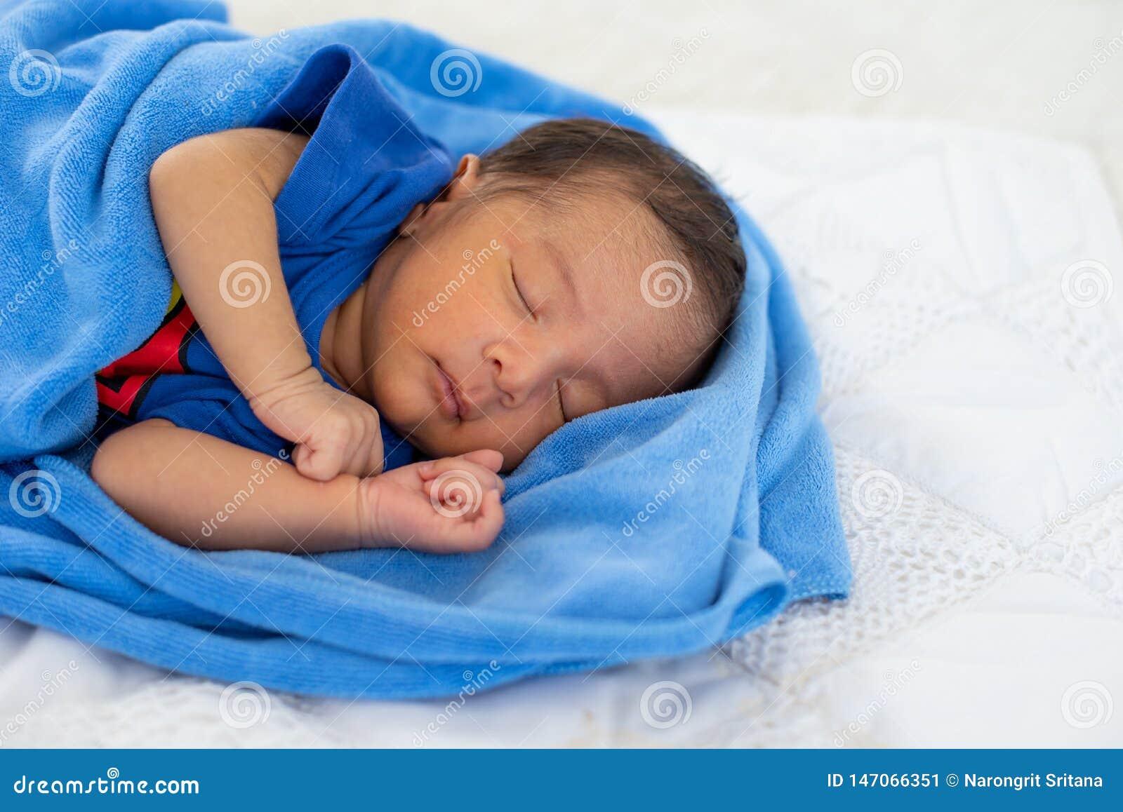 Il punto di vista alto vicino di giovane neonato asiatico sta dormendo con l asciugamano blu sul letto bianco nella camera da let