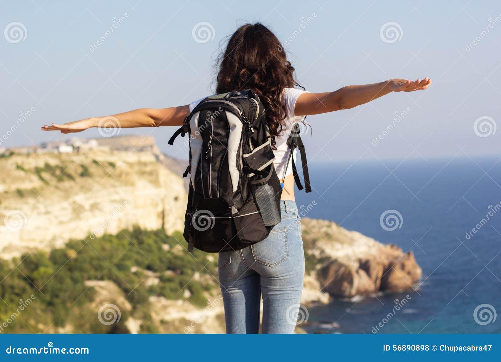 Il punto di vista posteriore del viaggiatore sta stando sulla roccia con lo zaino