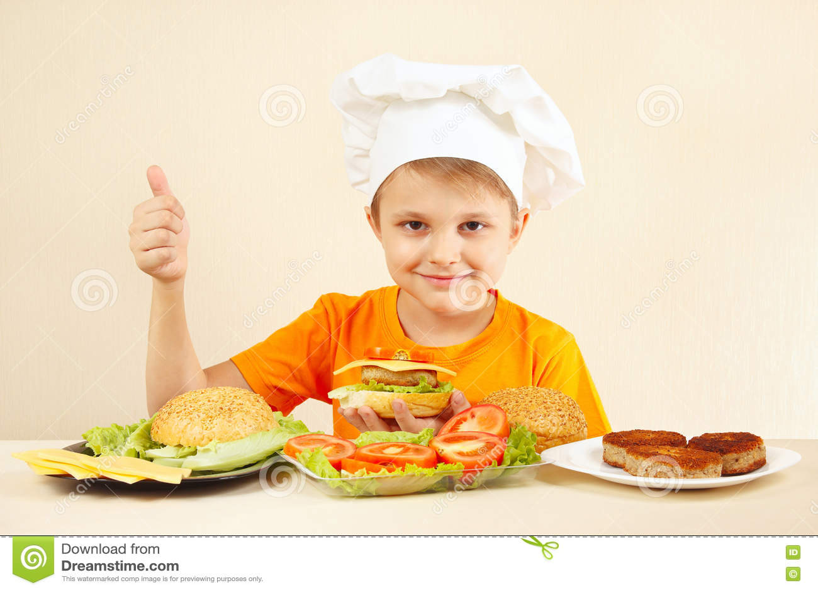 Il ragazzino in cappello dei cuochi unici mostra come cucinare l