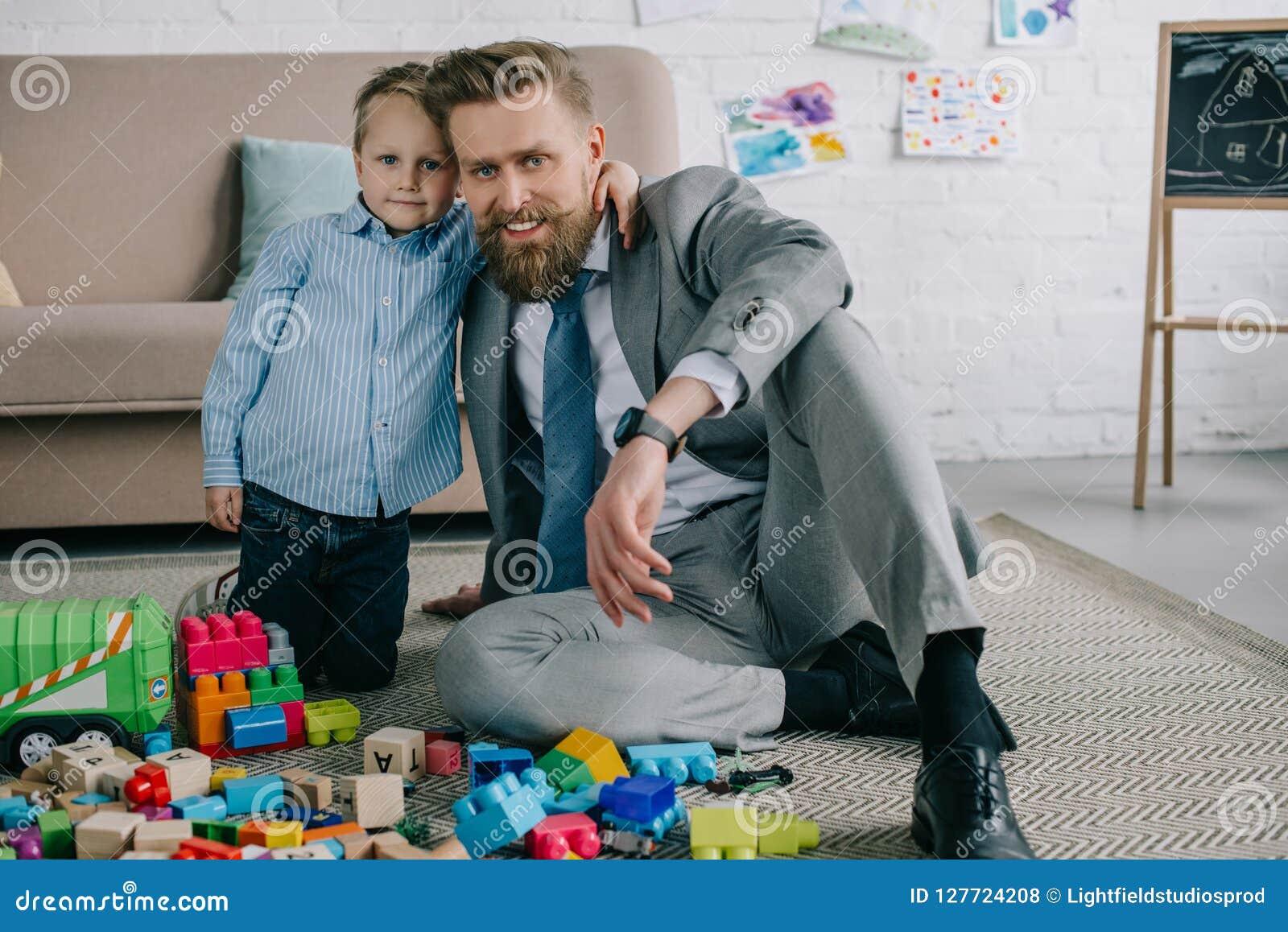 Il ragazzino che abbraccia il padre sorridente in vestito a casa lavora e vita