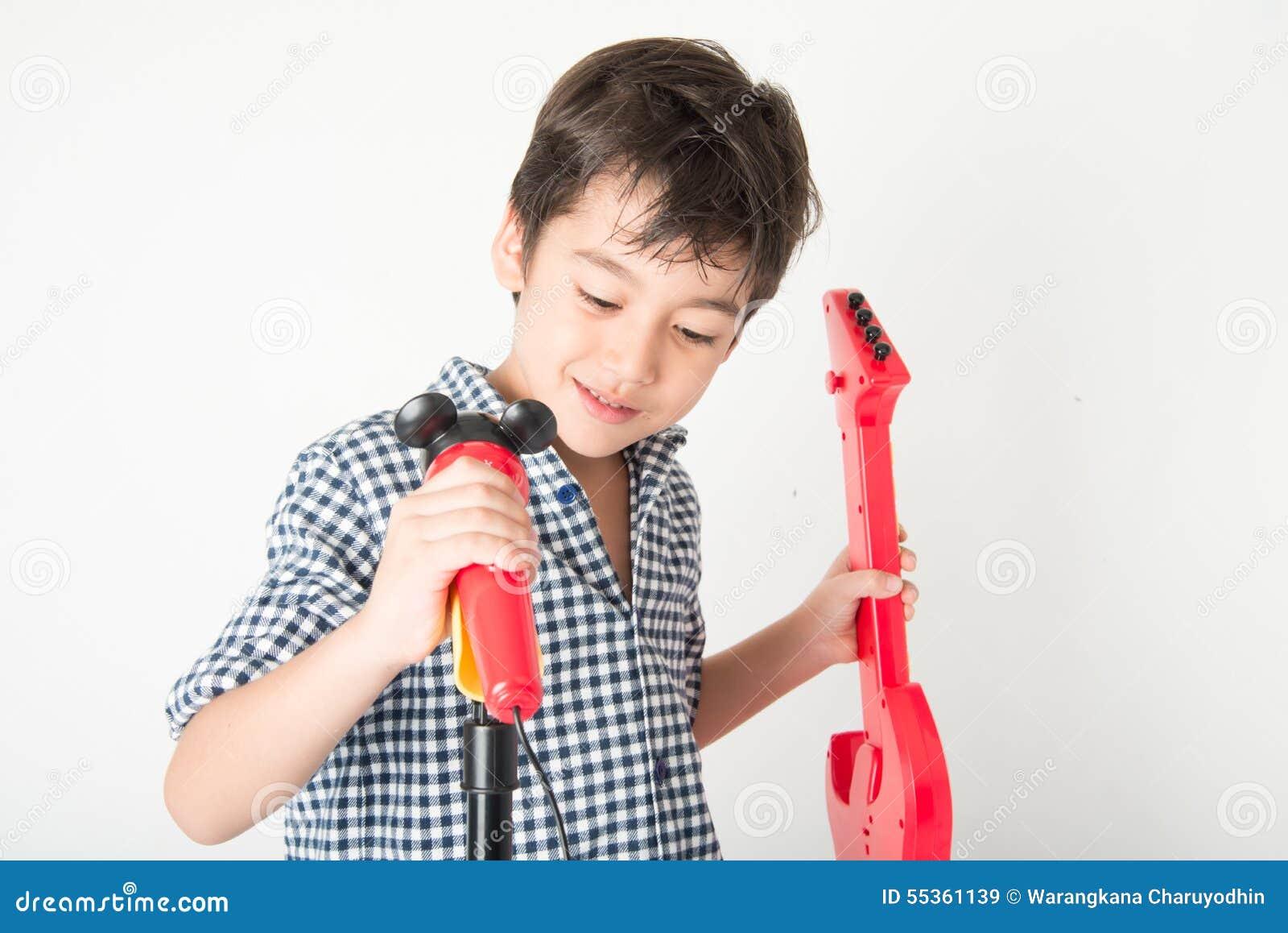 Il ragazzino che gioca la chitarra e canta con il microfono