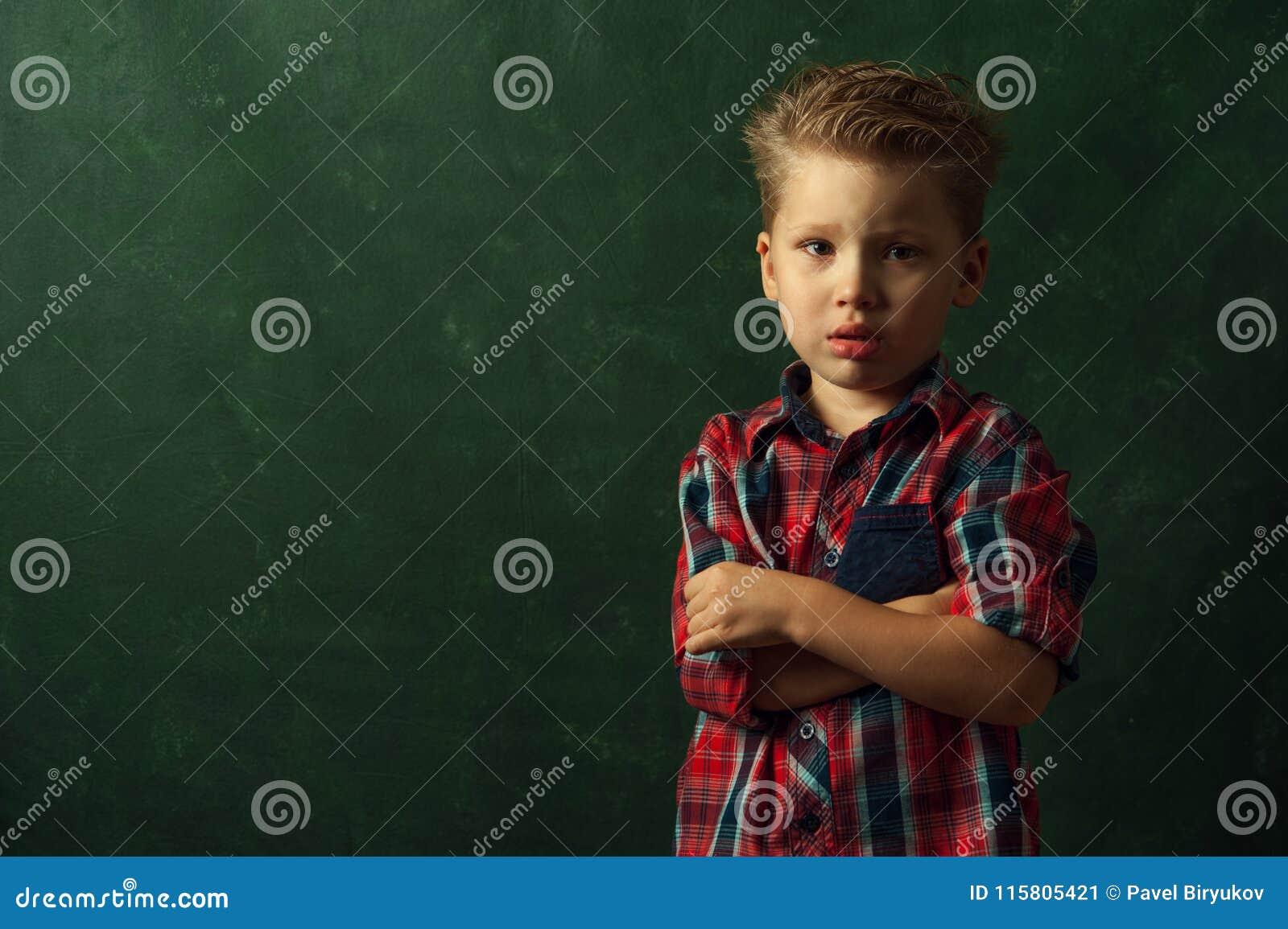 Il ragazzino confuso triste sta nell angolo scuro