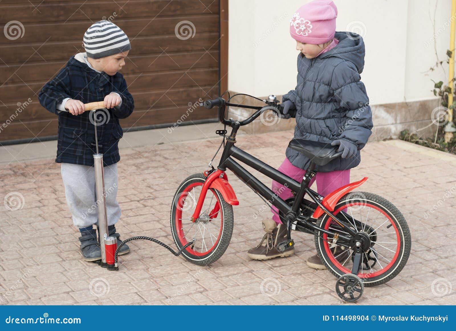 Il ragazzino e la ragazza riparano una bicicletta