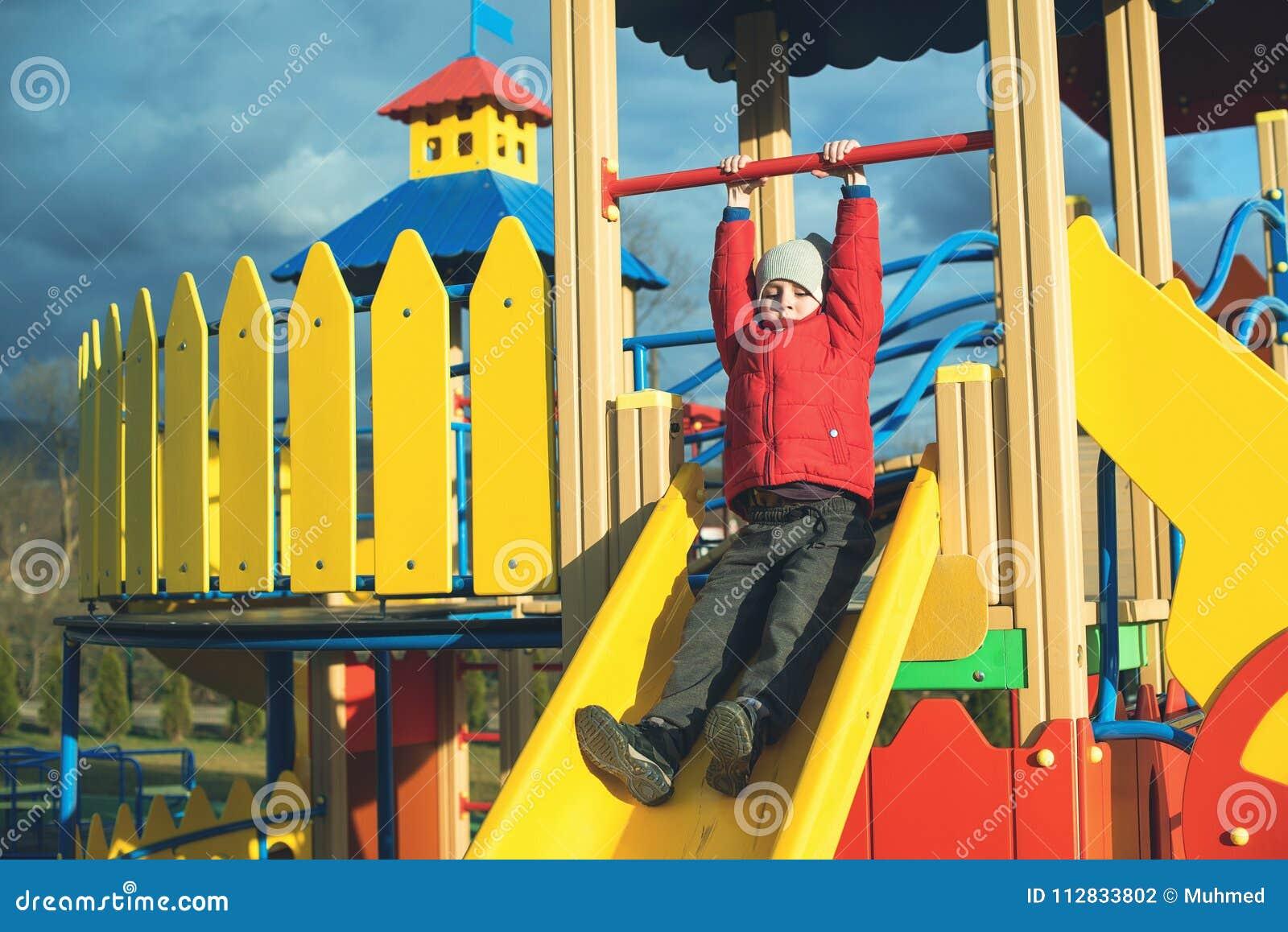 Il ragazzino felice si diverte e facendo scorrere sul campo da giuoco moderno variopinto in parco