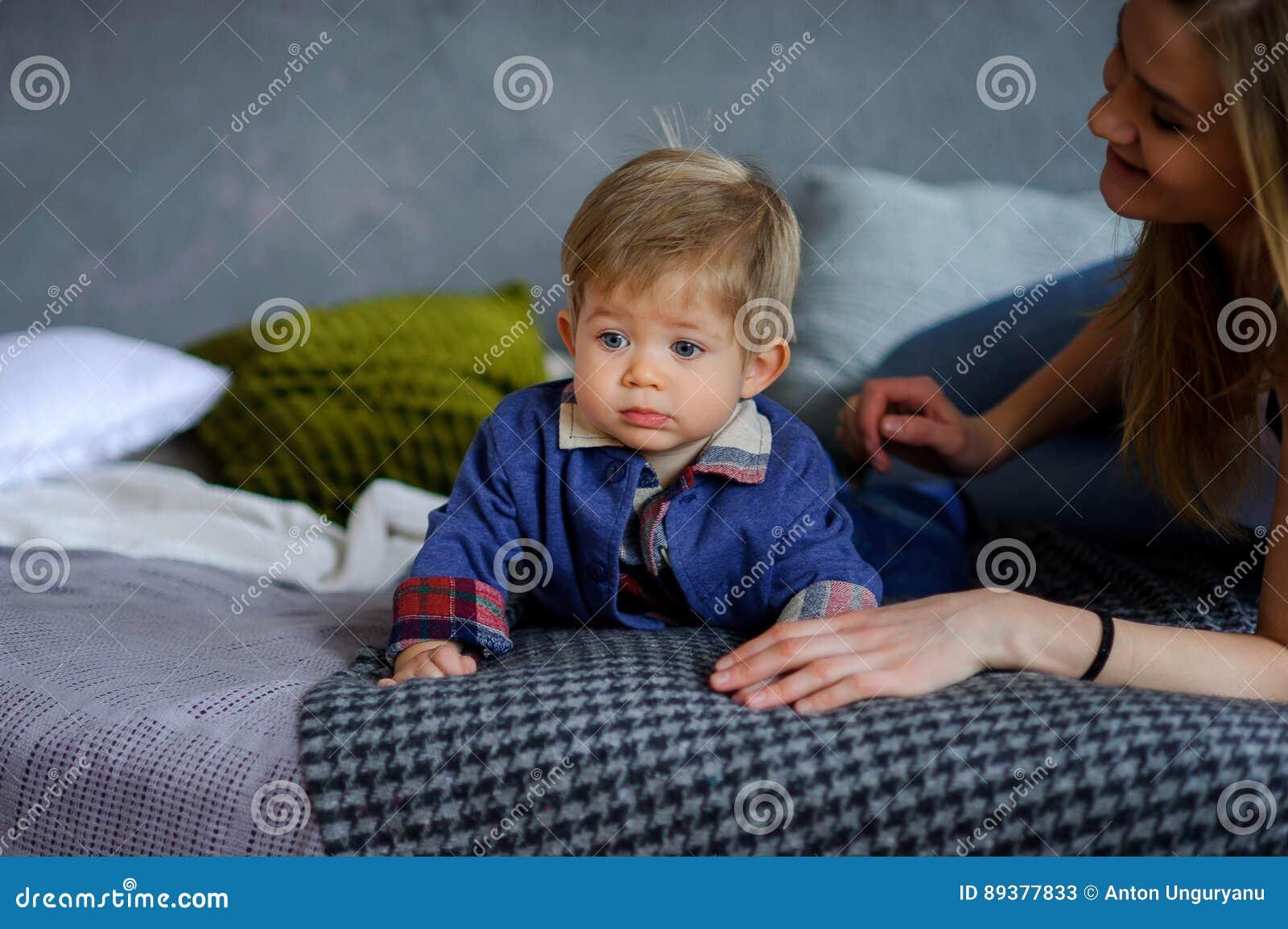 Il ragazzino in modo divertente si trova su un grande letto