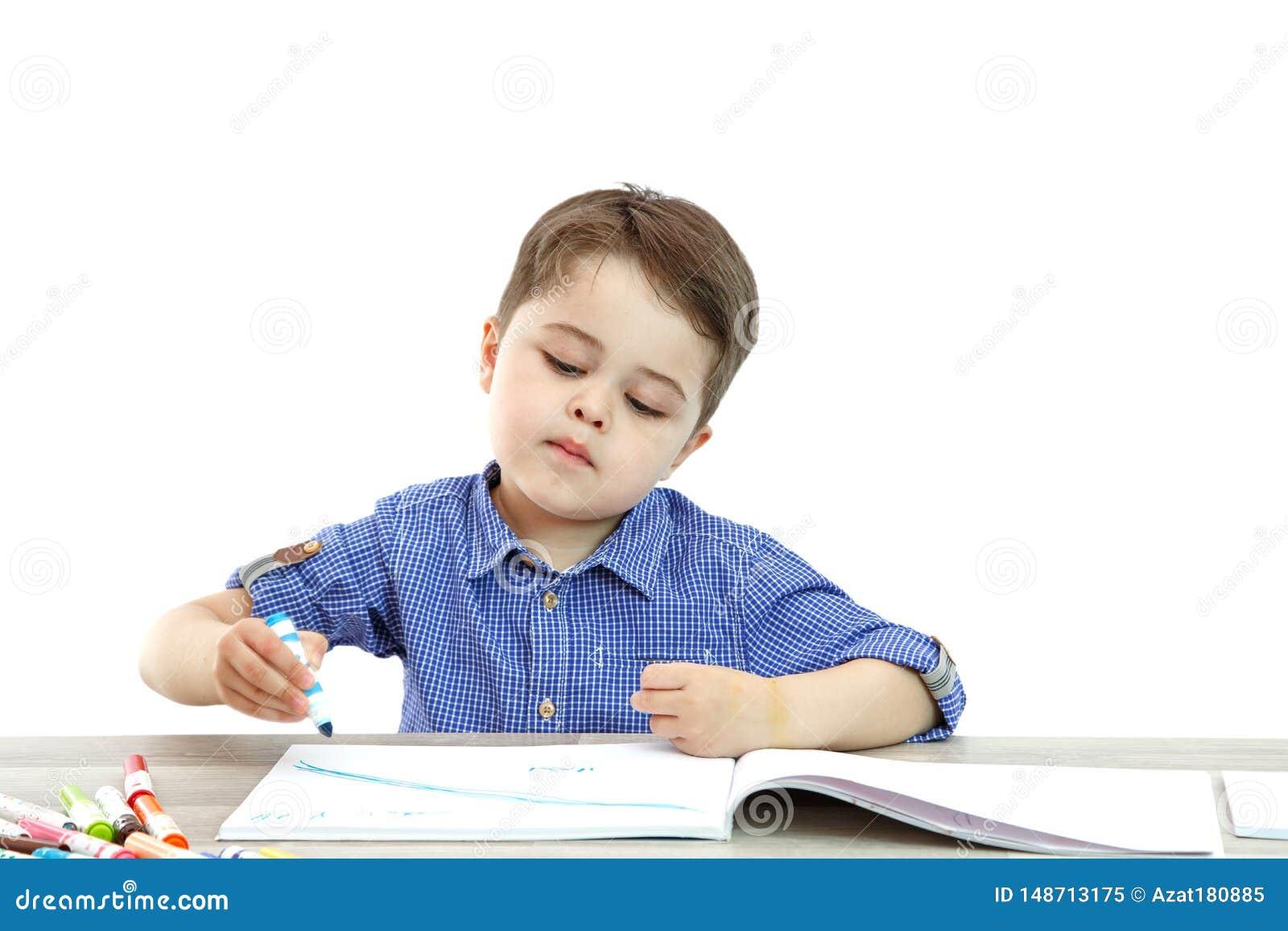 Il ragazzino si siede e disegna scrive su un fondo isolato