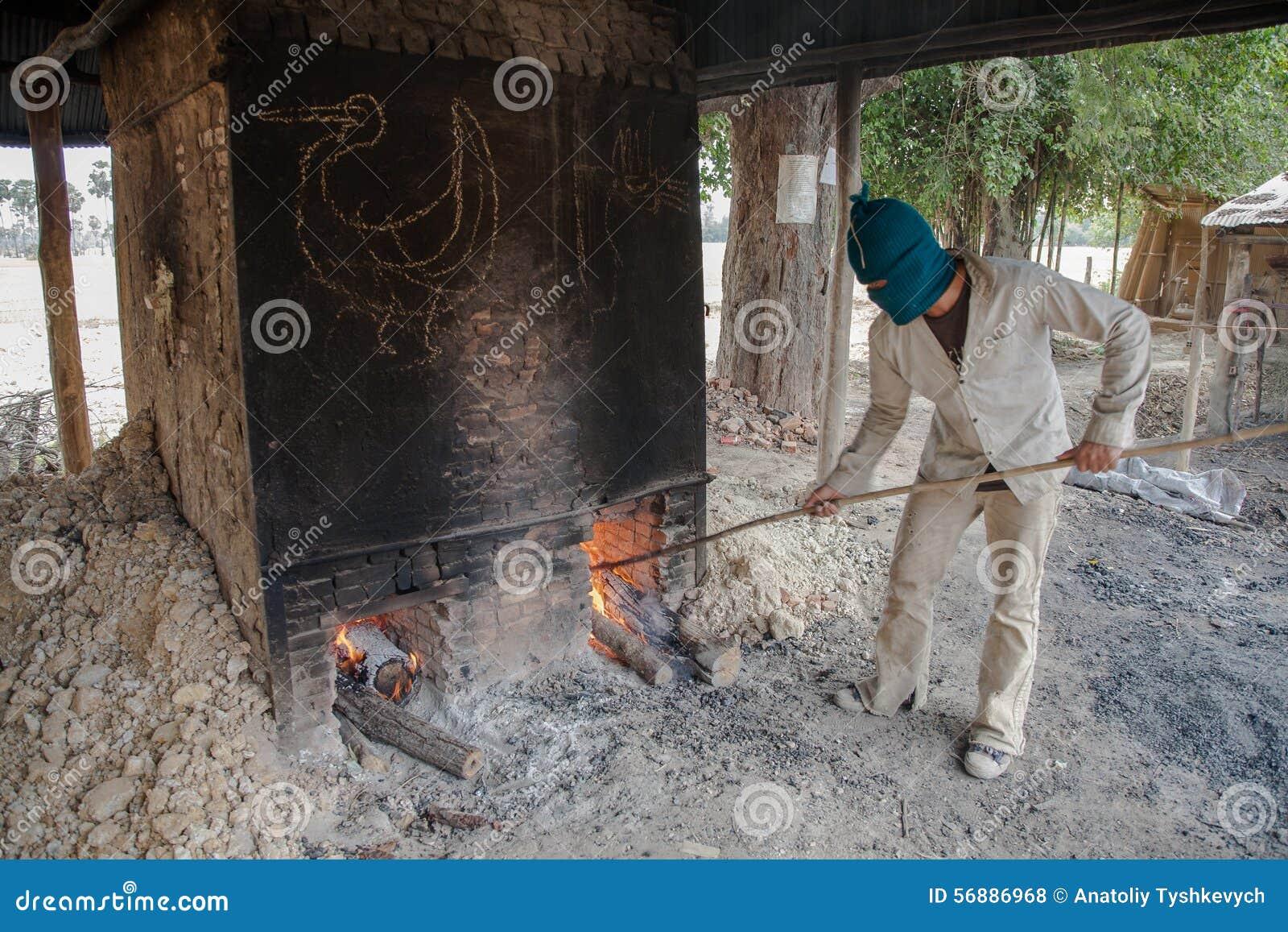 Il ragazzo anziano annega, fuligginoso, forno disponendo il legno e corregge il fuoco