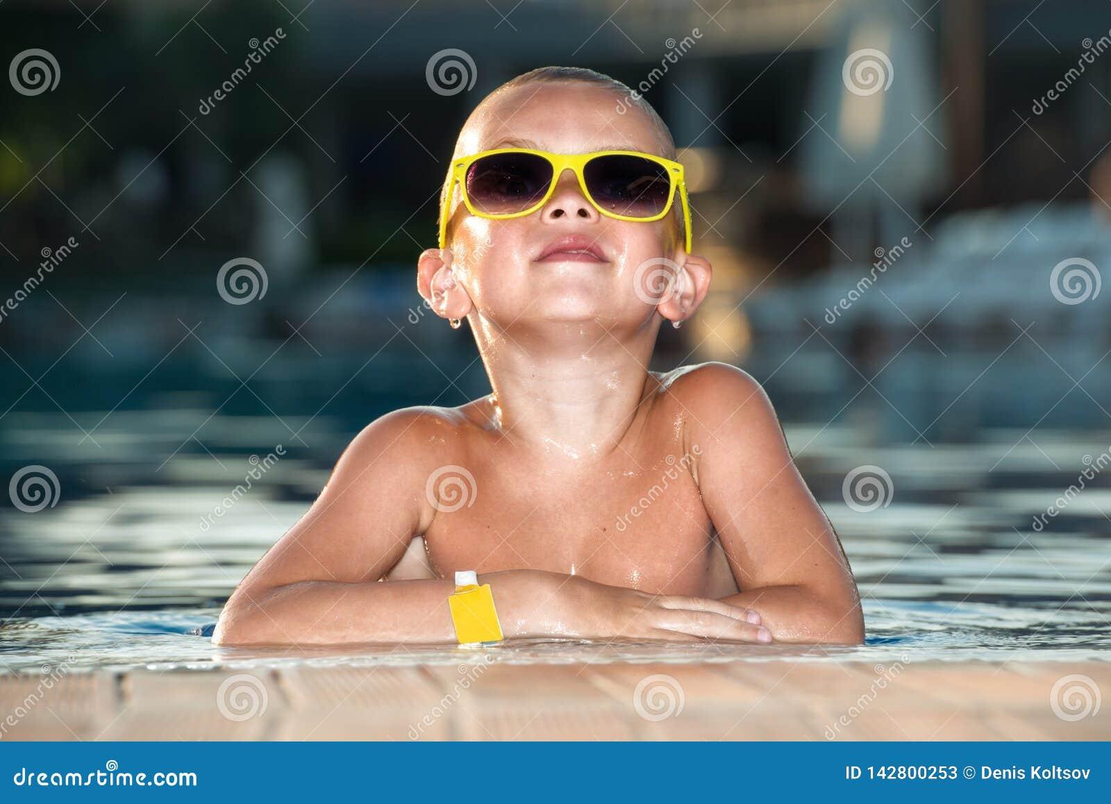 Il ragazzo con gli occhiali da sole che riposano nello stagno Vacanza di estate