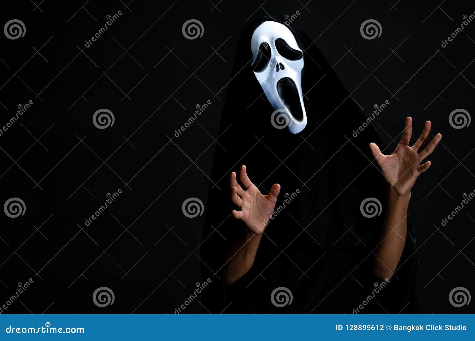 Il ragazzo in copertura nera con il cosplay bianco della maschera del fantasma a CA del diavolo
