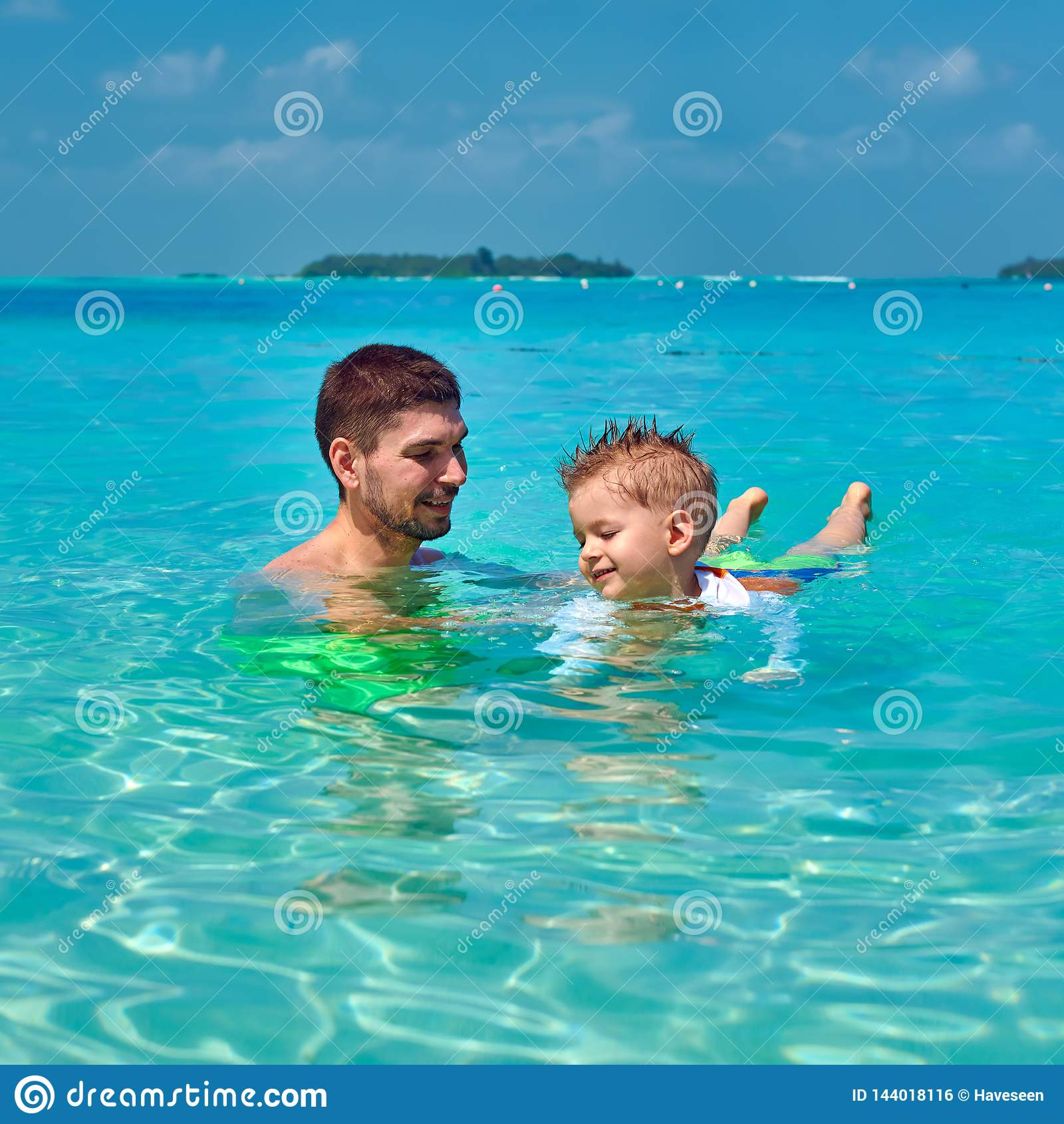 Il ragazzo del bambino impara nuotare con il padre
