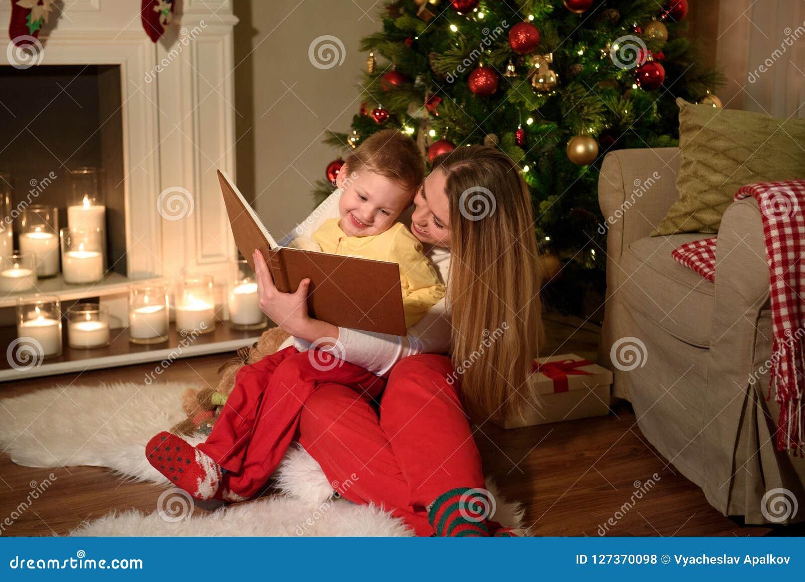 Il ragazzo e la sua mamma stanno leggendo un libro che ridono insieme