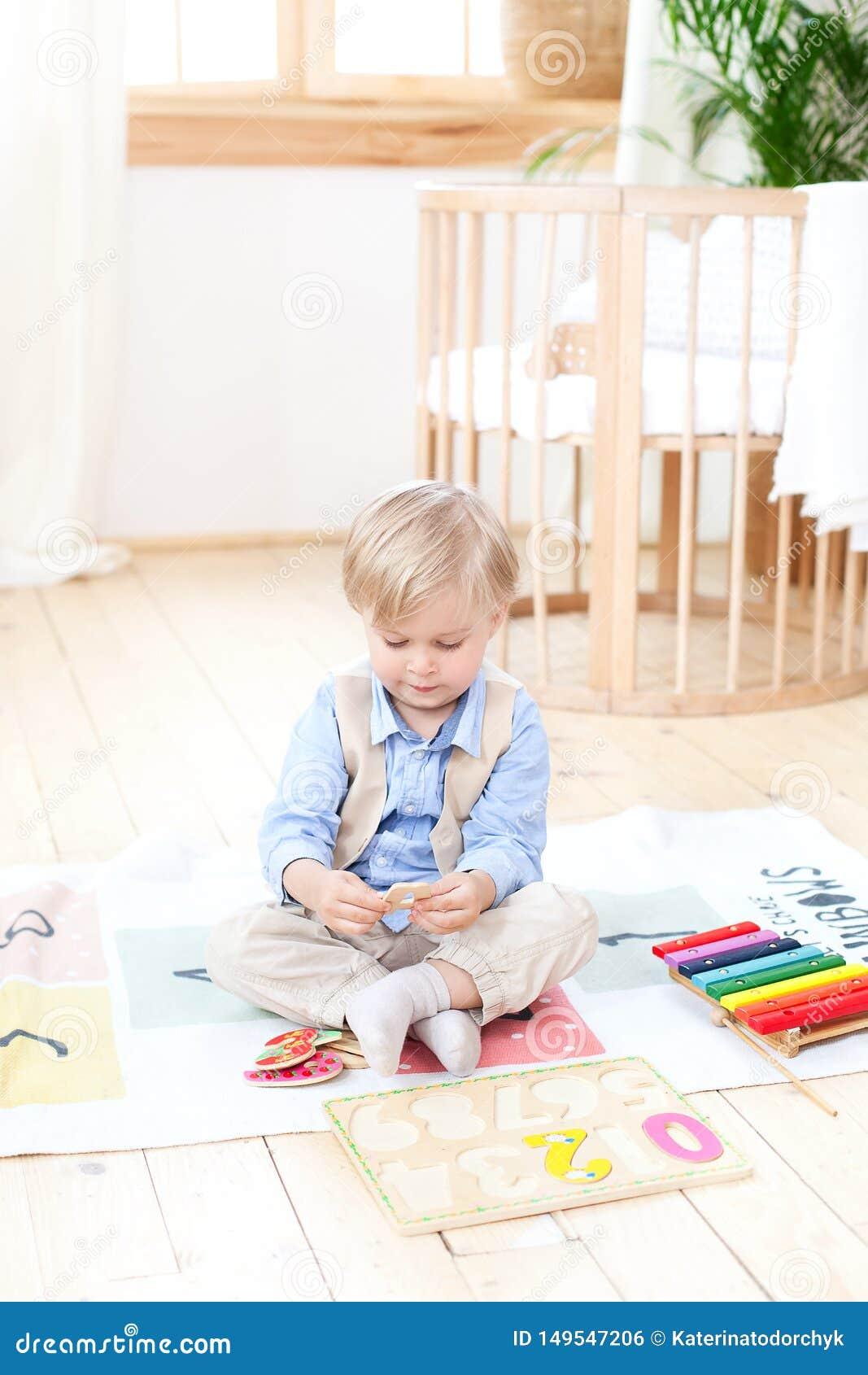 Il ragazzo gioca con i giocattoli di legno a casa Giocattoli di legno educativi per il bambino Ritratto di un ragazzo che si sied