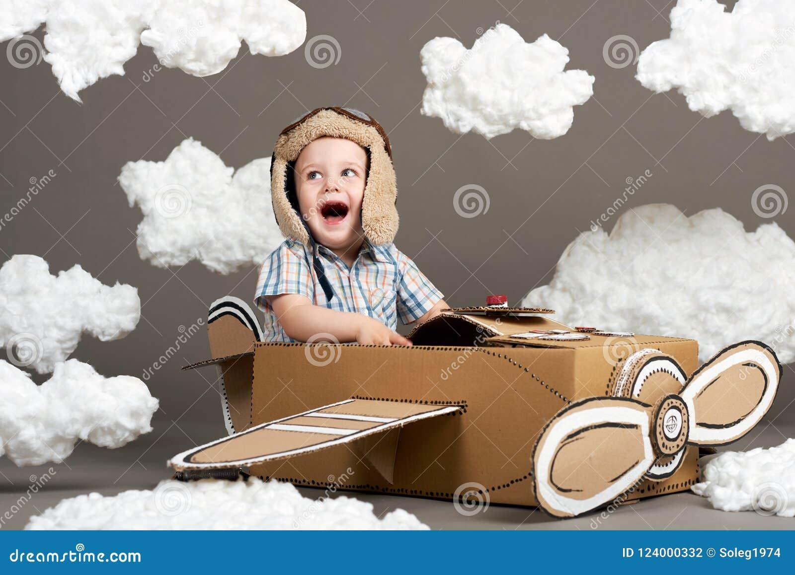 Il ragazzo gioca in un aeroplano fatto della scatola di cartone e dei sogni di diventare un pilota, nuvole da ovatta su un fondo