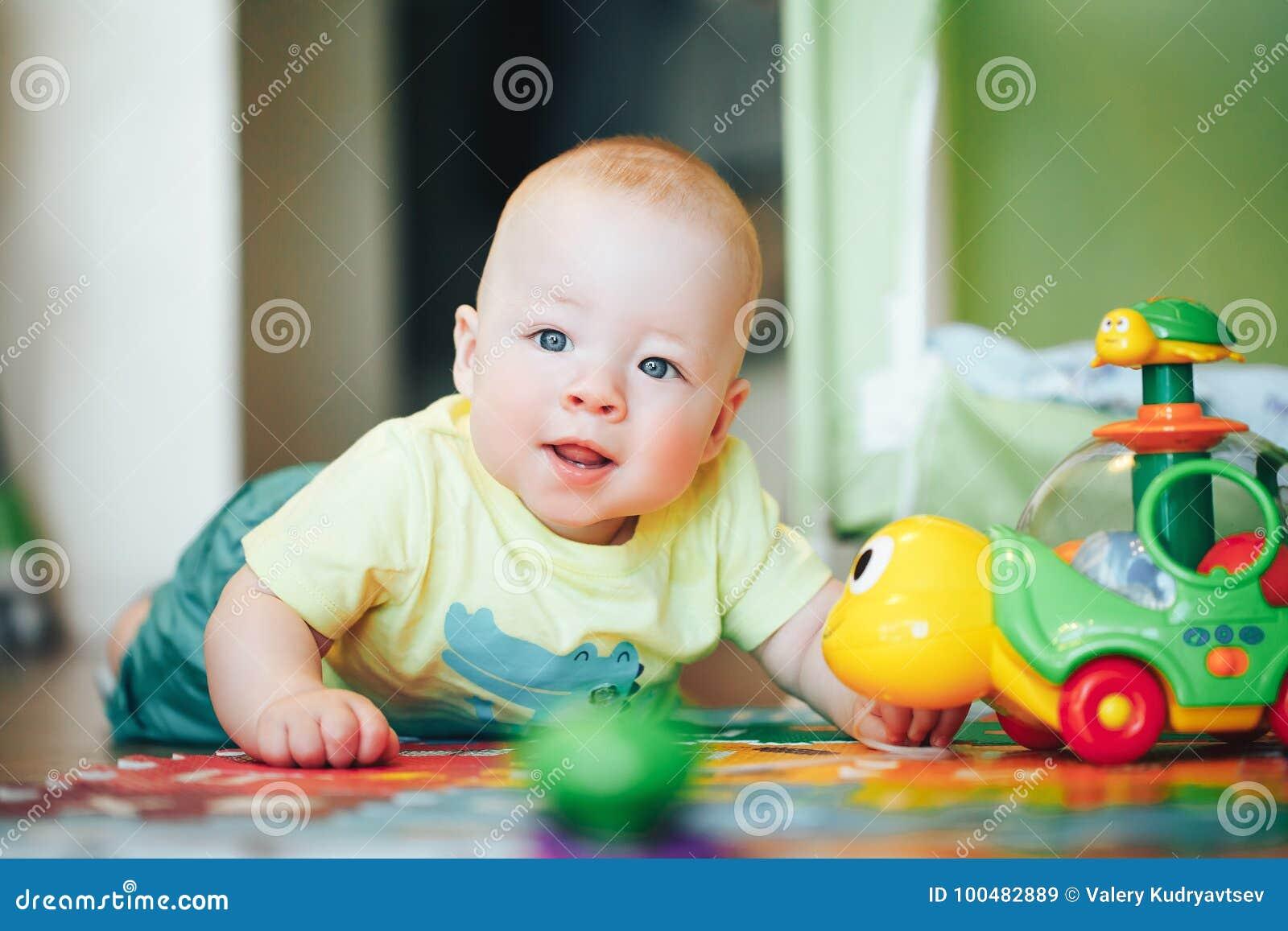 Il ragazzo infantile del bambino del bambino sei mesi sta giocando su un pavimento