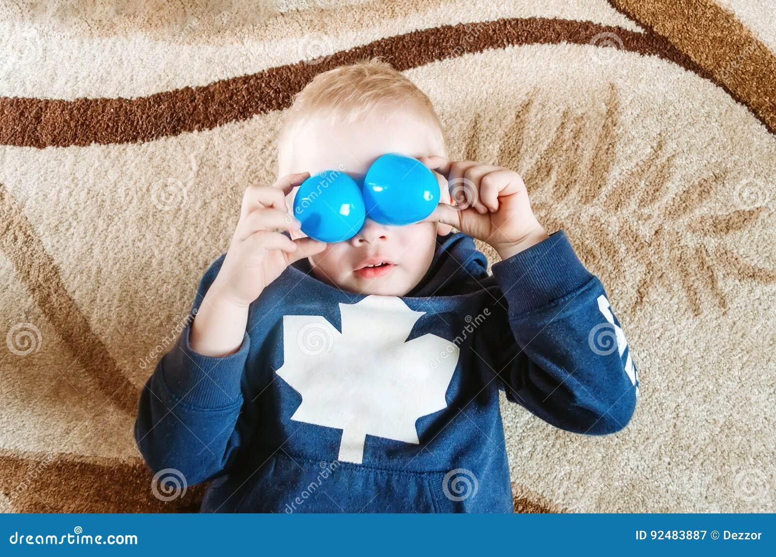 Il ragazzo si trova sul pavimento e mostra gli occhi divertenti con i giocattoli
