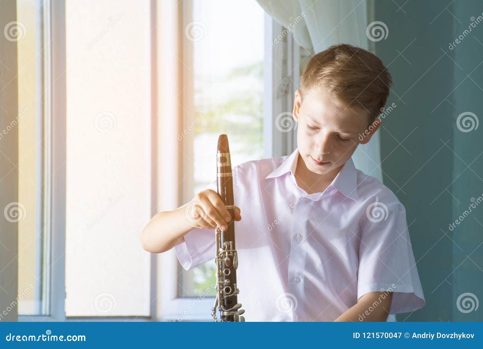 Il ragazzo sta facendo una pausa la finestra con un clarinetto nero Musicologia, istruzione di musica e istruzione