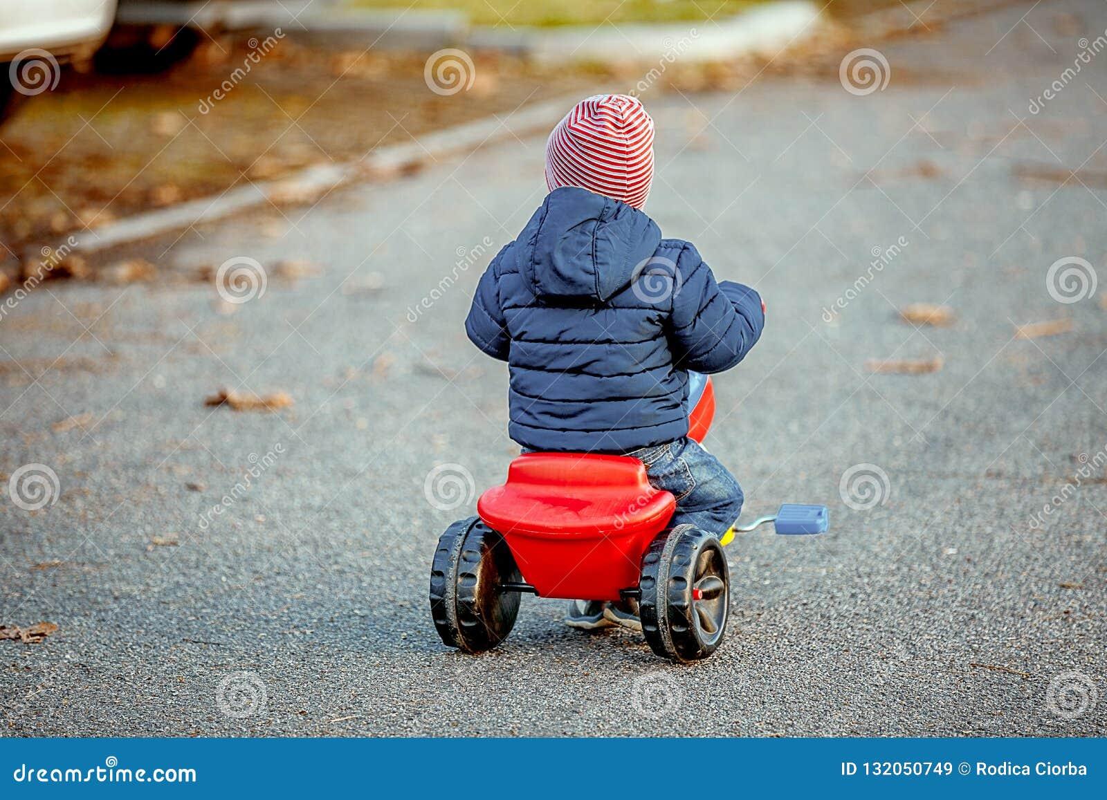 Il ragazzo sveglio del bambino in vestiti autunnali caldi ha girato da dietro divertiresi con il triciclo