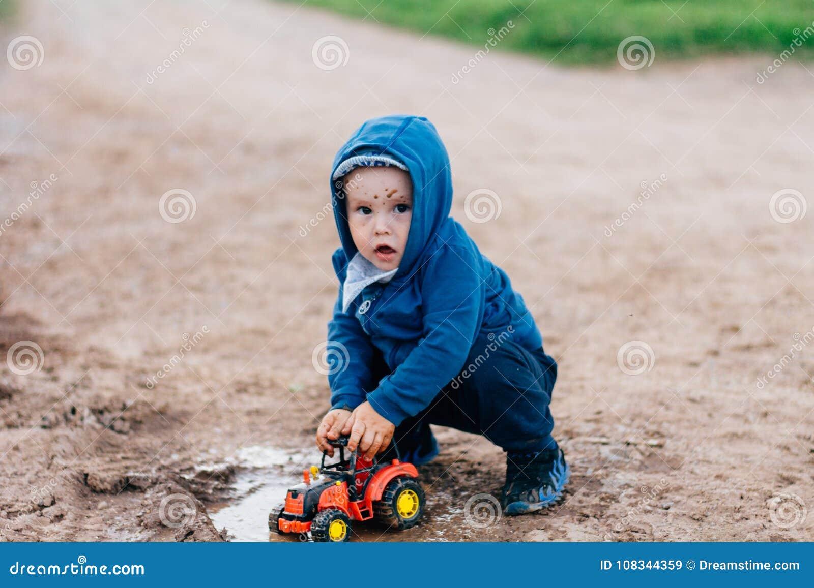 Il ragazzo in vestito blu gioca con un automobile del giocattolo nella sporcizia