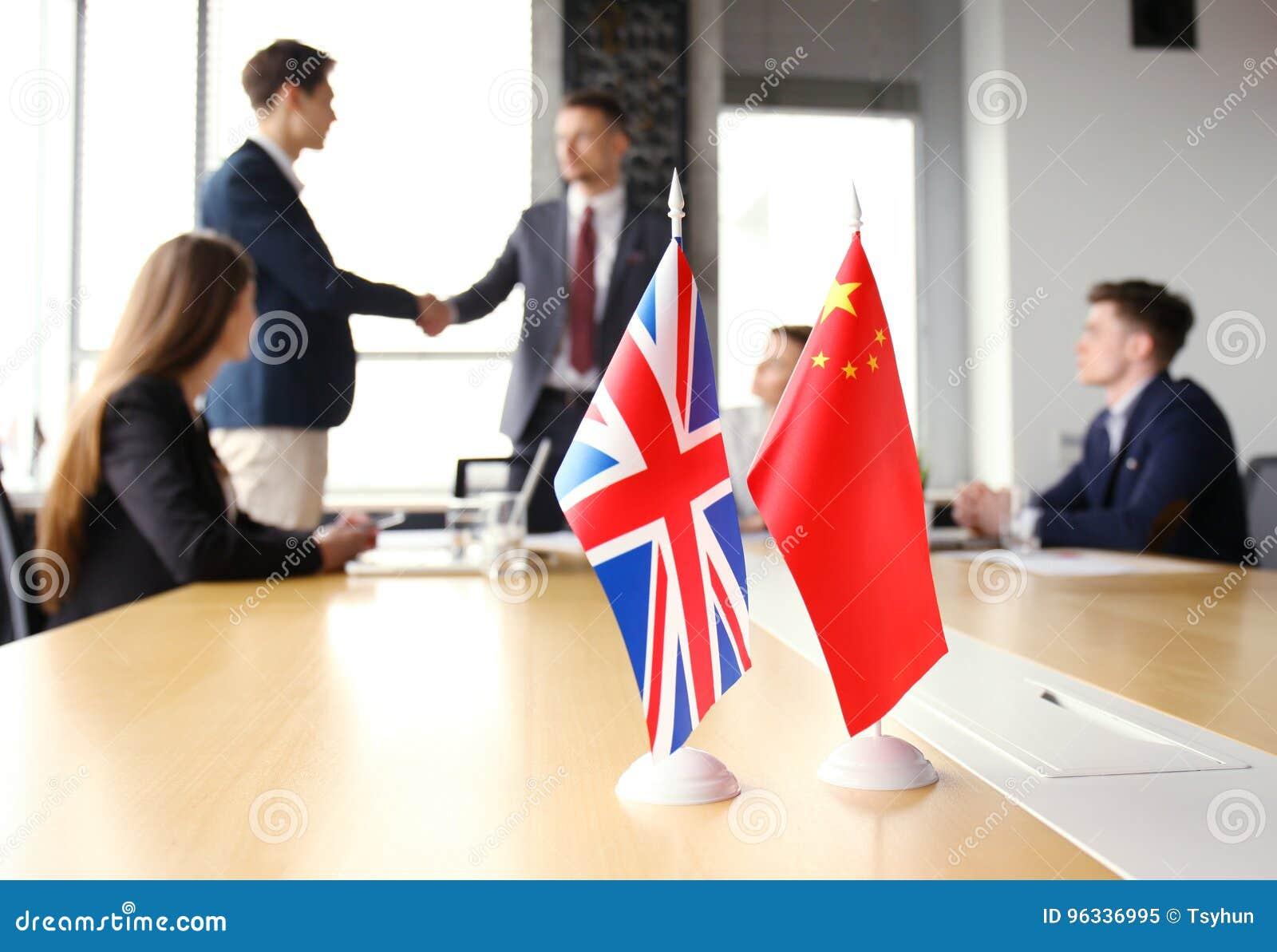 Il Regno Unito e capi cinesi che stringono le mani su un accordo di affare