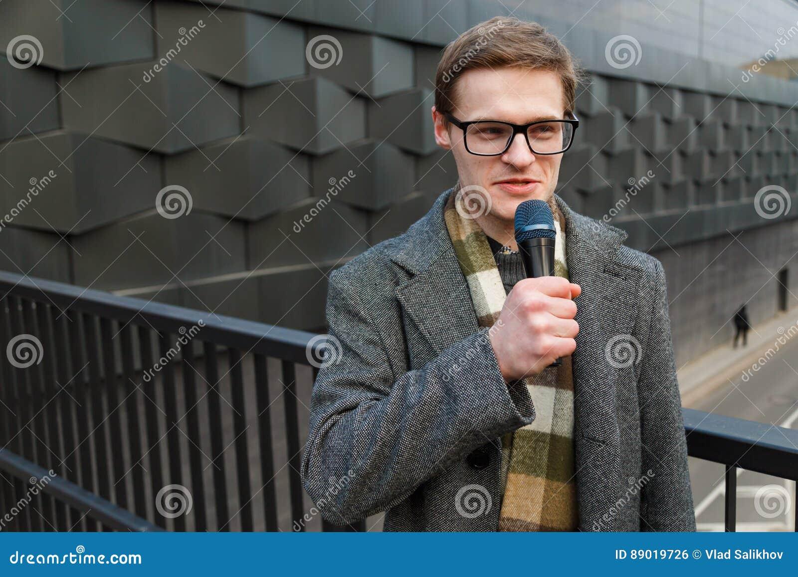 Il reporter professionista di notizie in occhiali con il microfono sta trasmettendo per radio sulla via Modo o notizie dal mondo