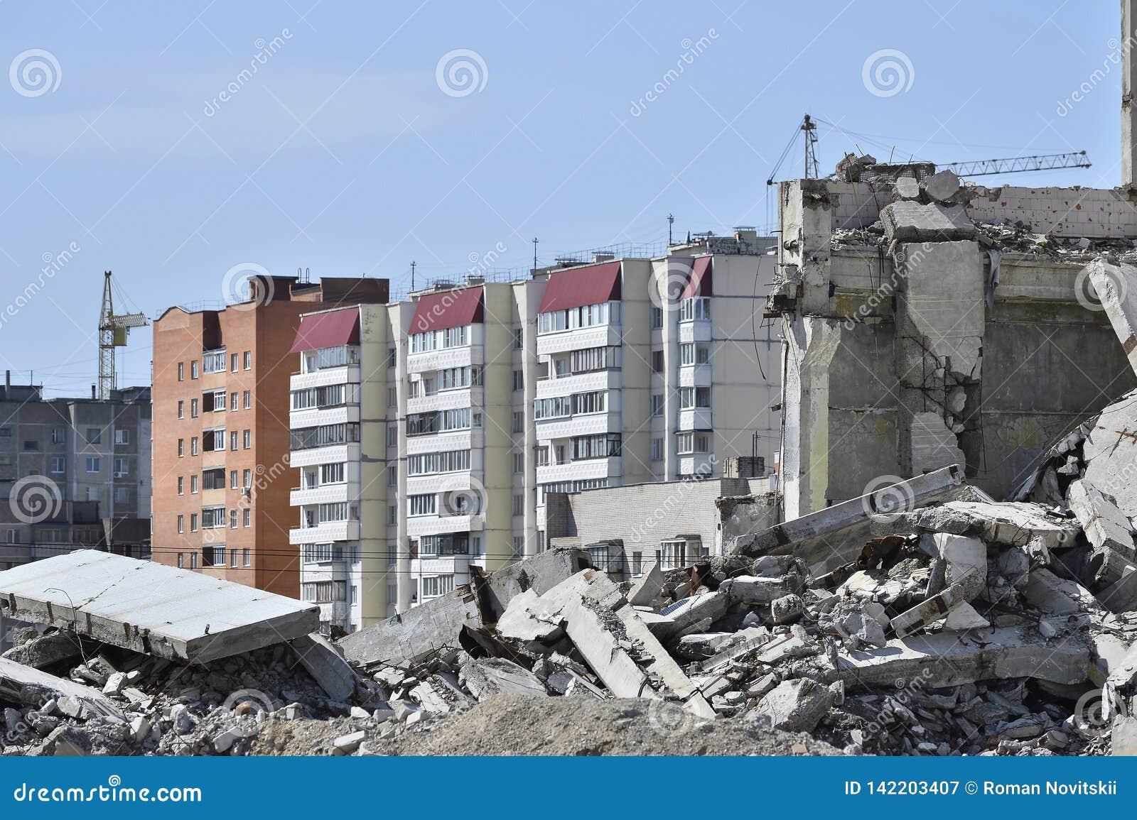 Il resti della struttura in cemento armato della costruzione contro la parte residenziale della città Concetto: distruzione e cre