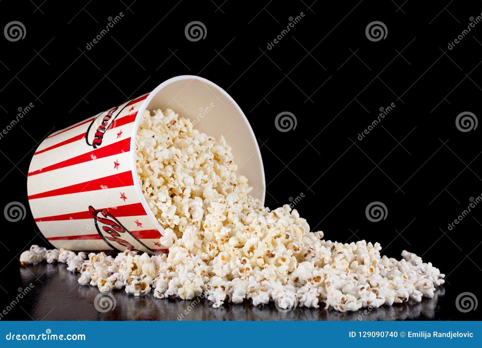 Il retro contenitore rosso e bianco di popcorn si è rovesciato sul nero