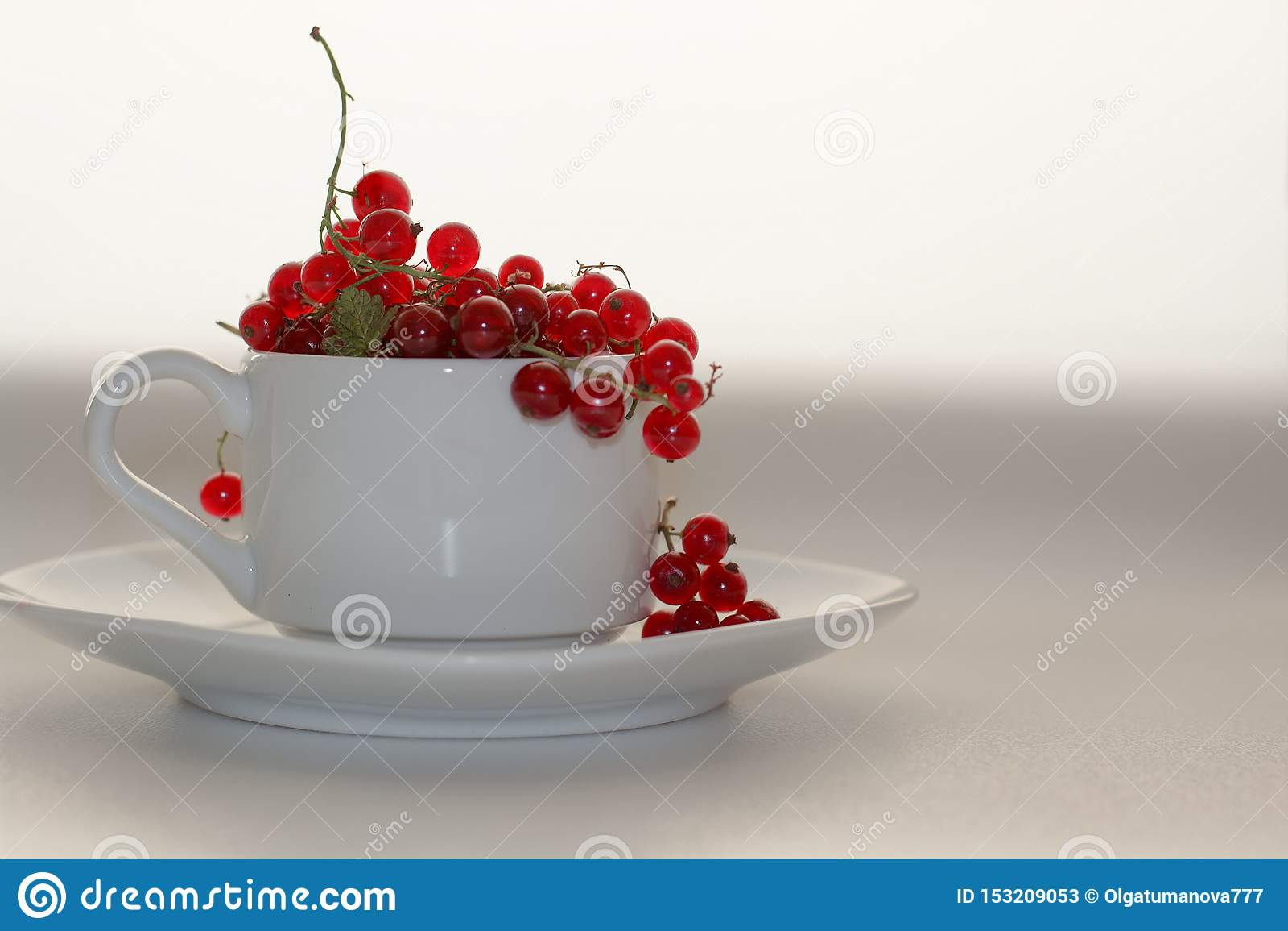 Il ribes rosso in una tazza bianca con un piattino su un fondo bianco summerred l uva passa in una tazza bianca con il piattino s