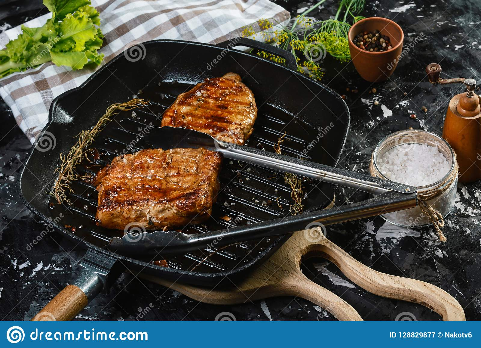 Il ribeye grigliato rinforza la bistecca sulla pentola del ferro con le erbe e le spezie Vista superiore con lo spazio della copi