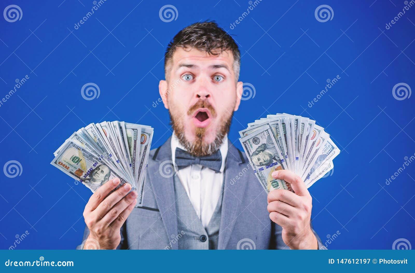 Il risultato sorpassava tutte le sue speranze Uomo barbuto che tiene denaro contante Uomo d affari ricco con le banconote dei dol