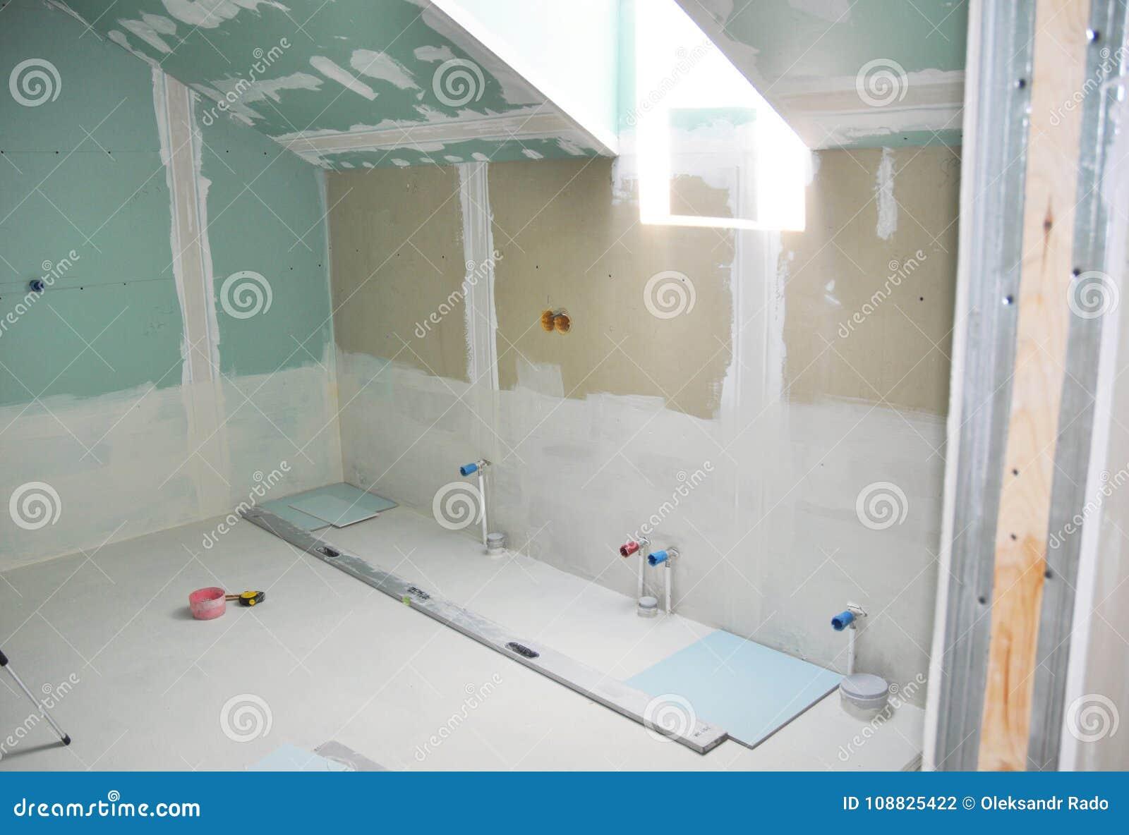 Il ritocco del bagno della soffitta con la riparazione del muro a secco, intonacante la pittura, stucco Riparazione e rinnovament