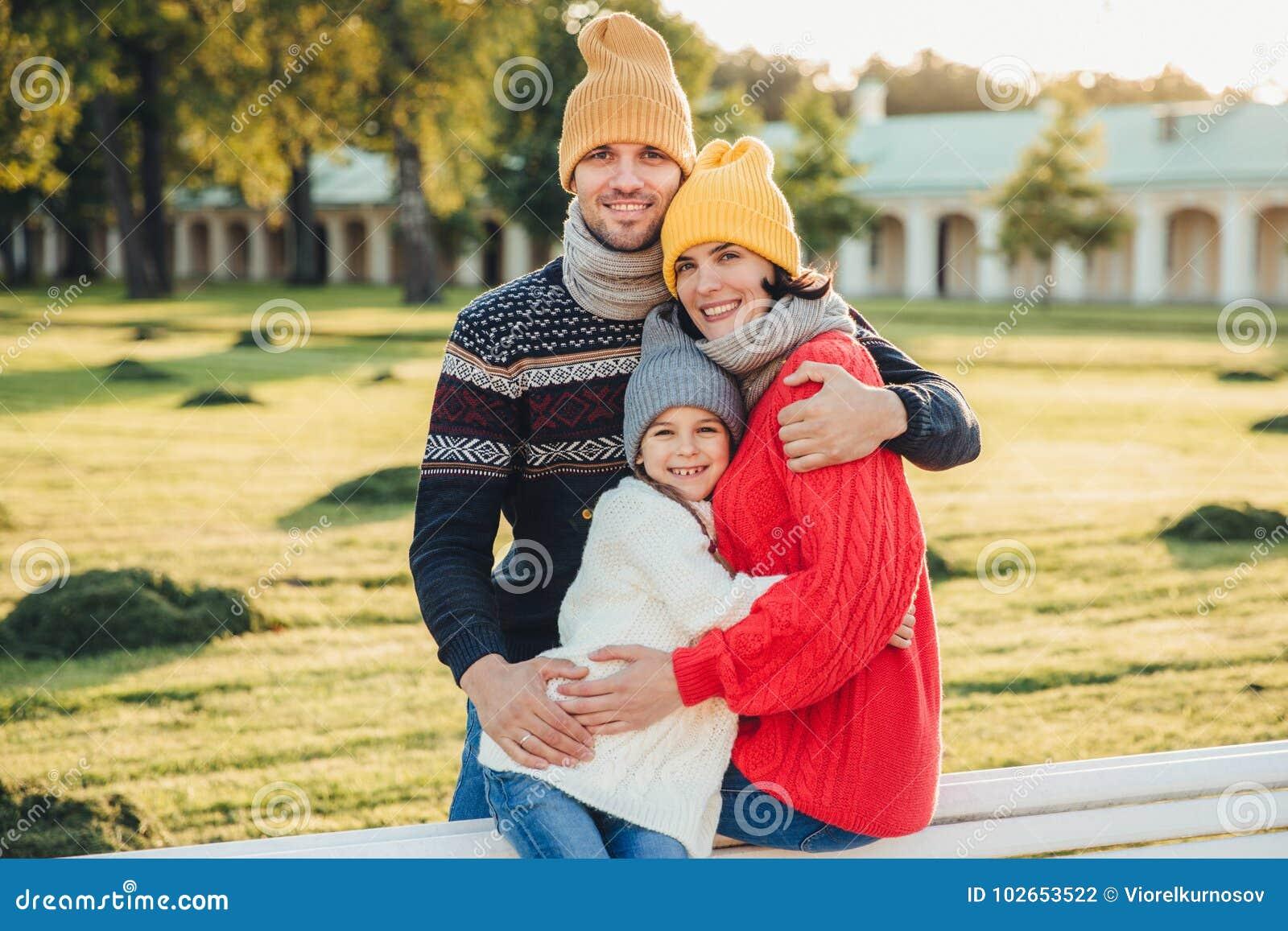 Il ritratto all aperto di bella donna sorridente, l uomo bello e la loro piccola figlia sveglia stanno insieme contro la i bildui