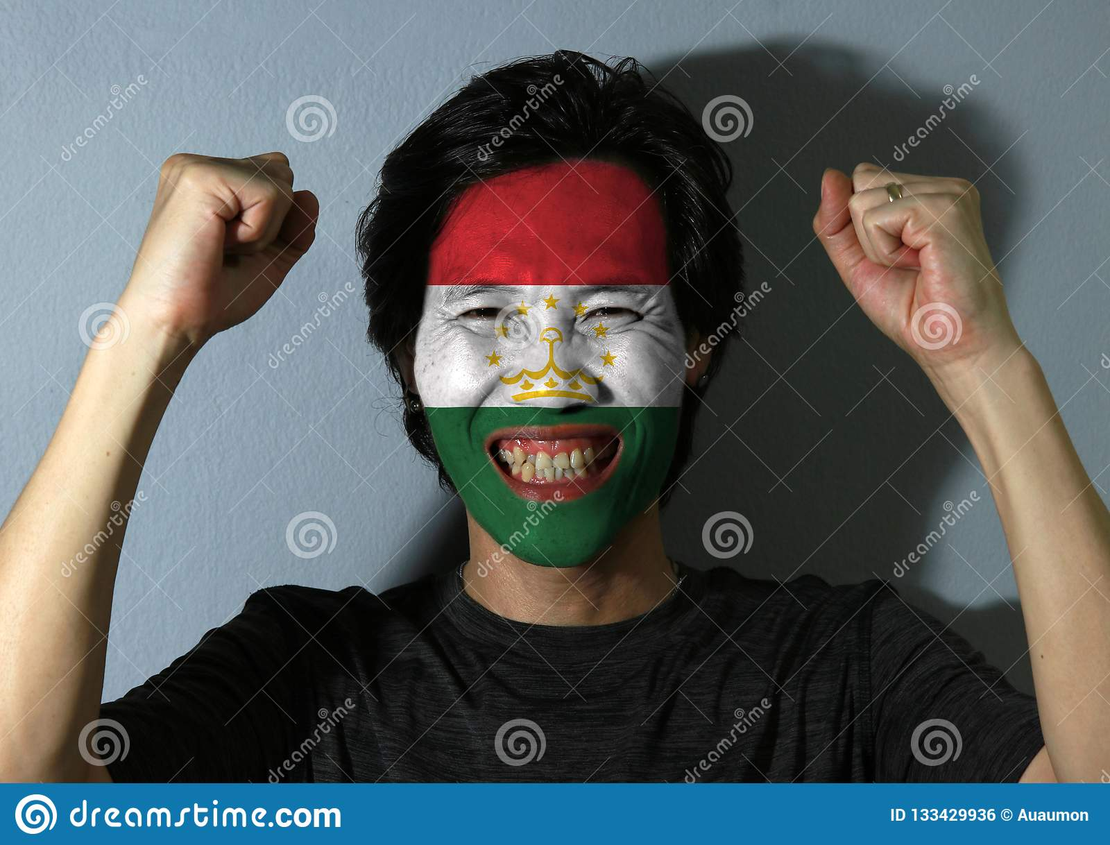 Il ritratto allegro di un uomo con la bandiera del Tagikistan ha dipinto sul suo fronte su fondo grigio Il concetto dello sport
