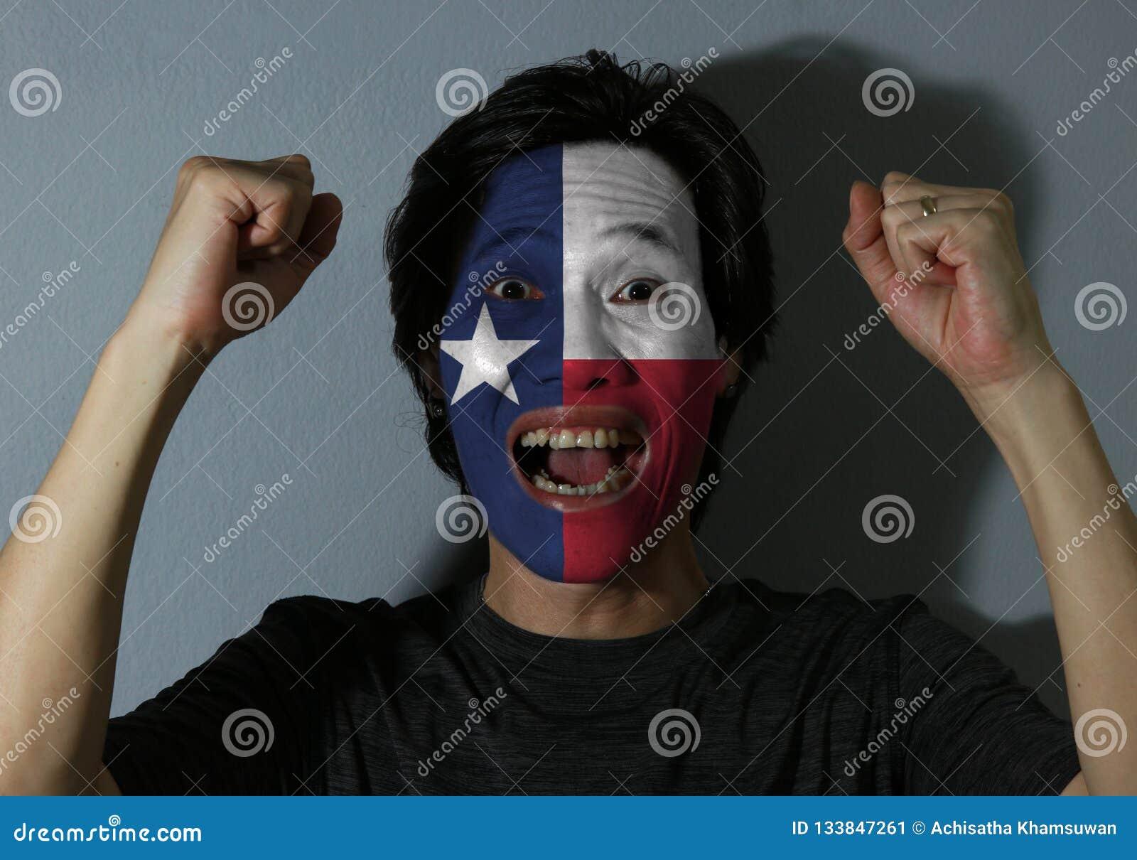 Il ritratto allegro di un uomo con la bandiera del Texas ha dipinto sul suo fronte su fondo grigio Il concetto dello sport o del
