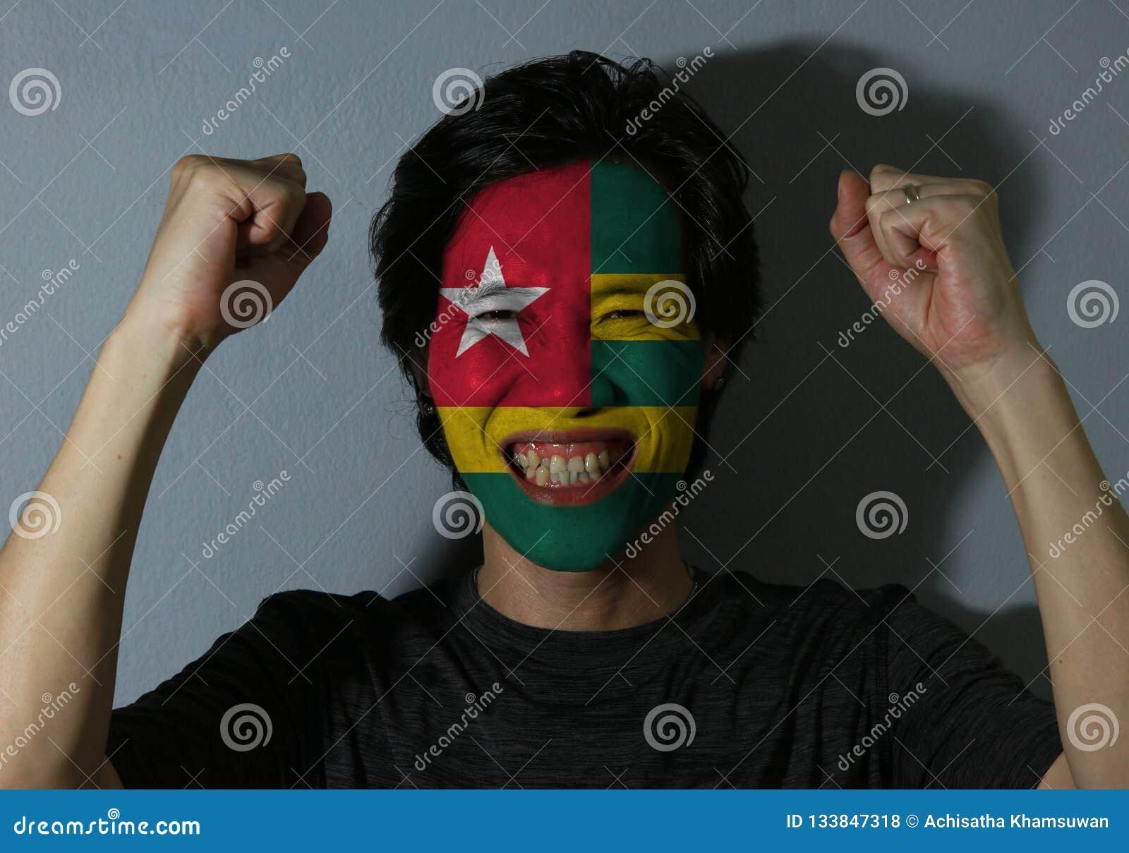 Il ritratto allegro di un uomo con la bandiera del Togo ha dipinto sul suo fronte su fondo grigio Il concetto dello sport o del n