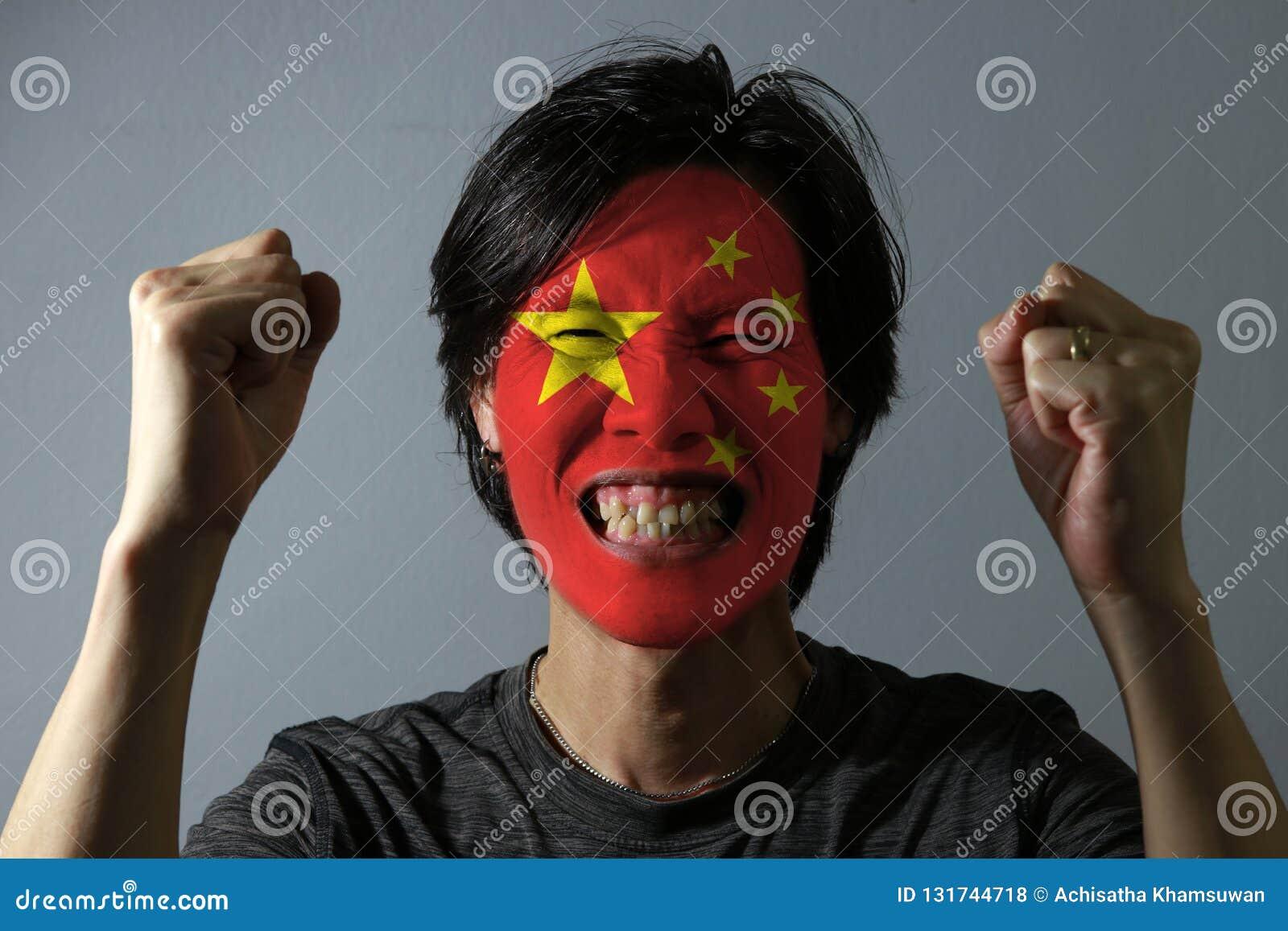 Il ritratto allegro di un uomo con la bandiera della Cina ha dipinto sul suo fronte su fondo grigio Il concetto dello sport o del