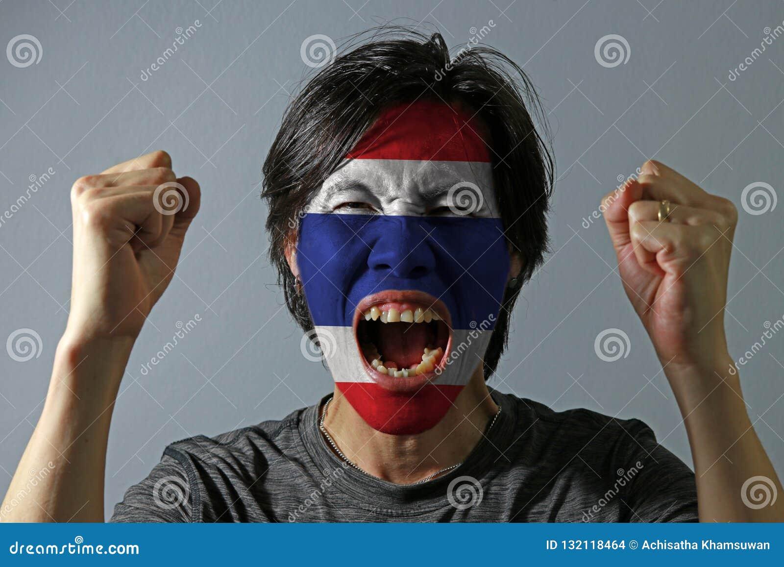 Il ritratto allegro di un uomo con la bandiera della Tailandia ha dipinto sul suo fronte su fondo grigio