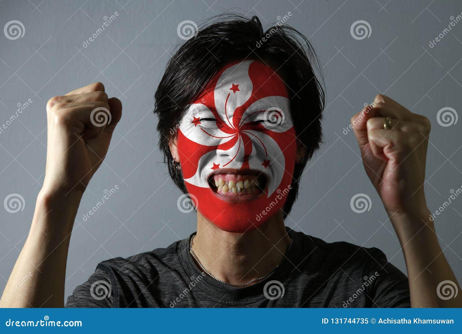 Il ritratto allegro di un uomo con la bandiera di Hong Kong ha dipinto sul suo fronte su fondo grigio Il concetto dello sport