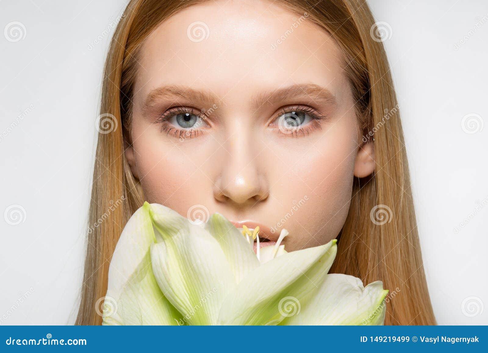 Il ritratto alto vicino di giovane modello femminile con pelle perfetta ed i bei occhi, grande fiore bianco riguarda la parte del