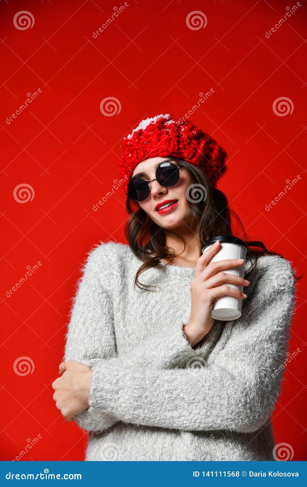 Il ritratto alto vicino di una ragazza sorridente nella tenuta del cappello porta via la tazza di caffè