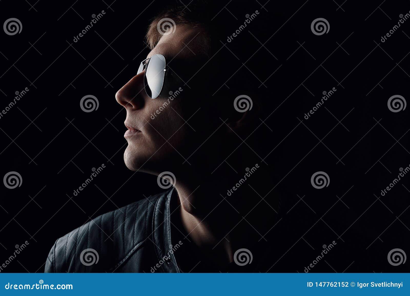 Il ritratto del giovane Primo piano del giovane serio in bomber nero ed occhiali da sole su fondo scuro