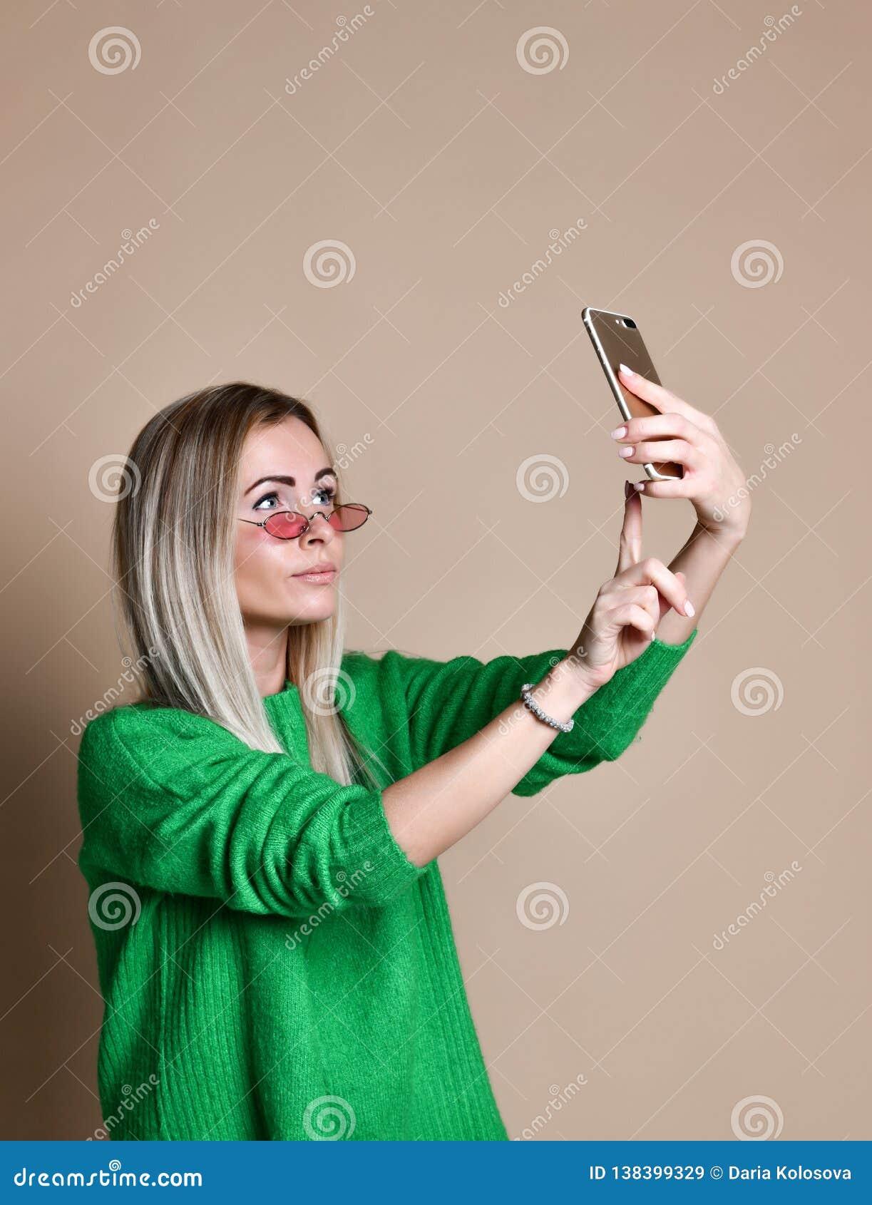 Il ritratto del primo piano della donna bionda di giovane modo allegro nell usura del maglione fa il selfie sullo smartphone, sop