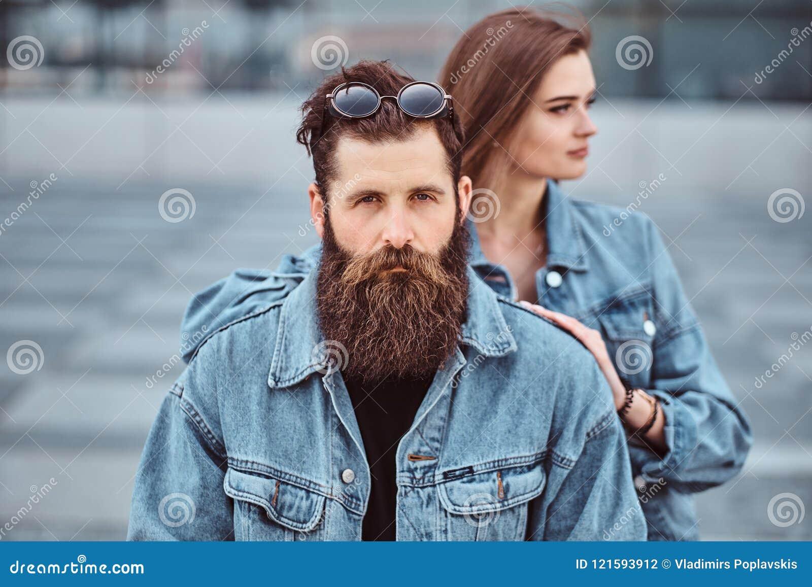 Il ritratto del primo piano di una coppia dei pantaloni a vita bassa di un maschio barbuto brutale e della sua amica si è vestito