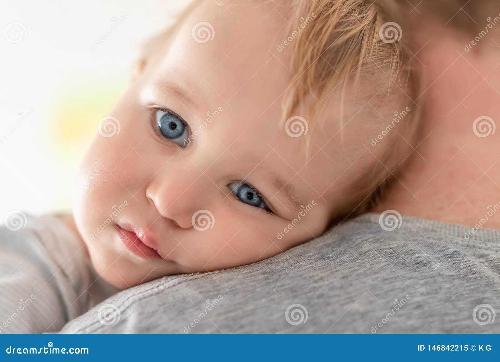 Il ritratto del primo piano del ragazzo caucasico biondo adorabile sveglio del bambino sui padri mette all interno Sicurezza rite