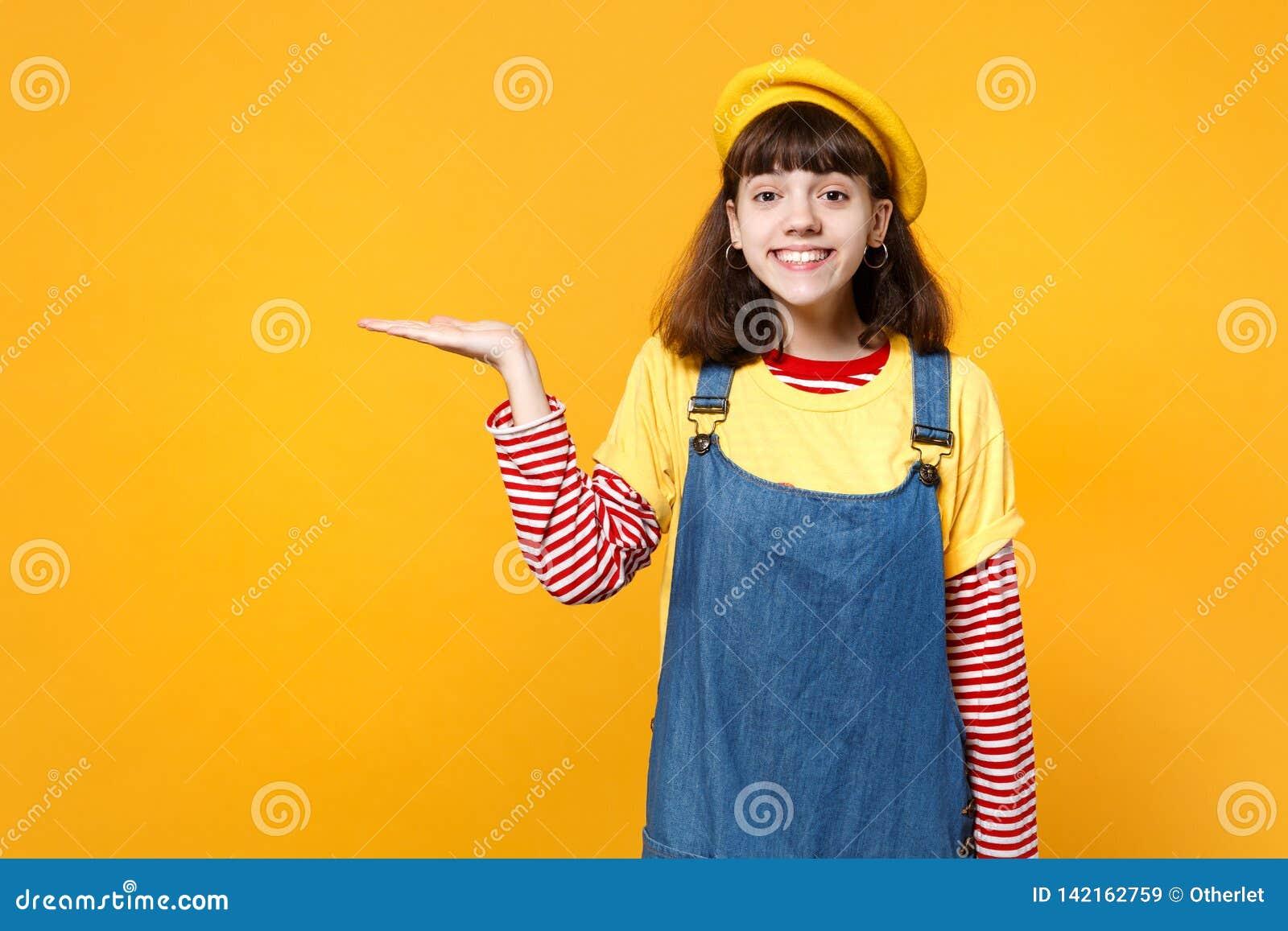 Il ritratto dell adolescente grazioso della ragazza in prendisole francesi del denim e del berretto che indica la mano da parte h