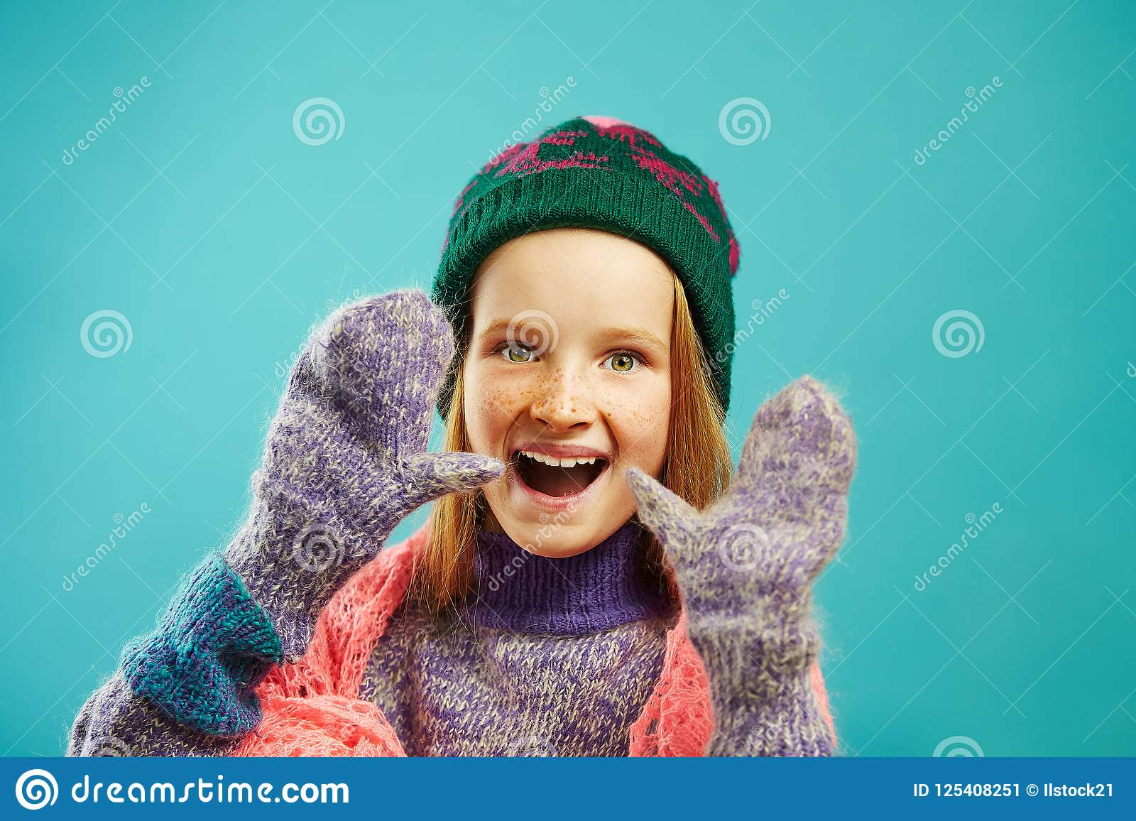 Il ritratto della ragazza allegra del bambino porta i guanti dell inverno, il maglione caldo, il cappello con il pompon e la scia