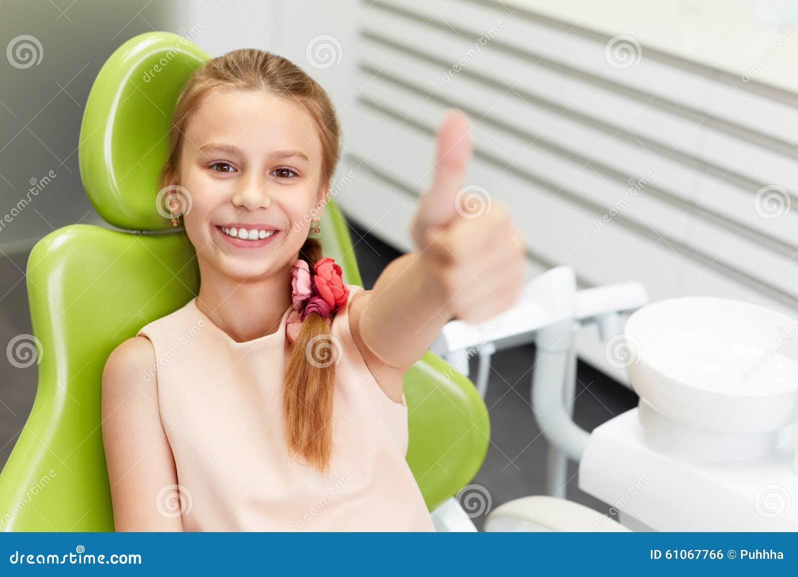 Il ritratto della ragazza felice mostra il pollice sul gesto alla clinica dentaria