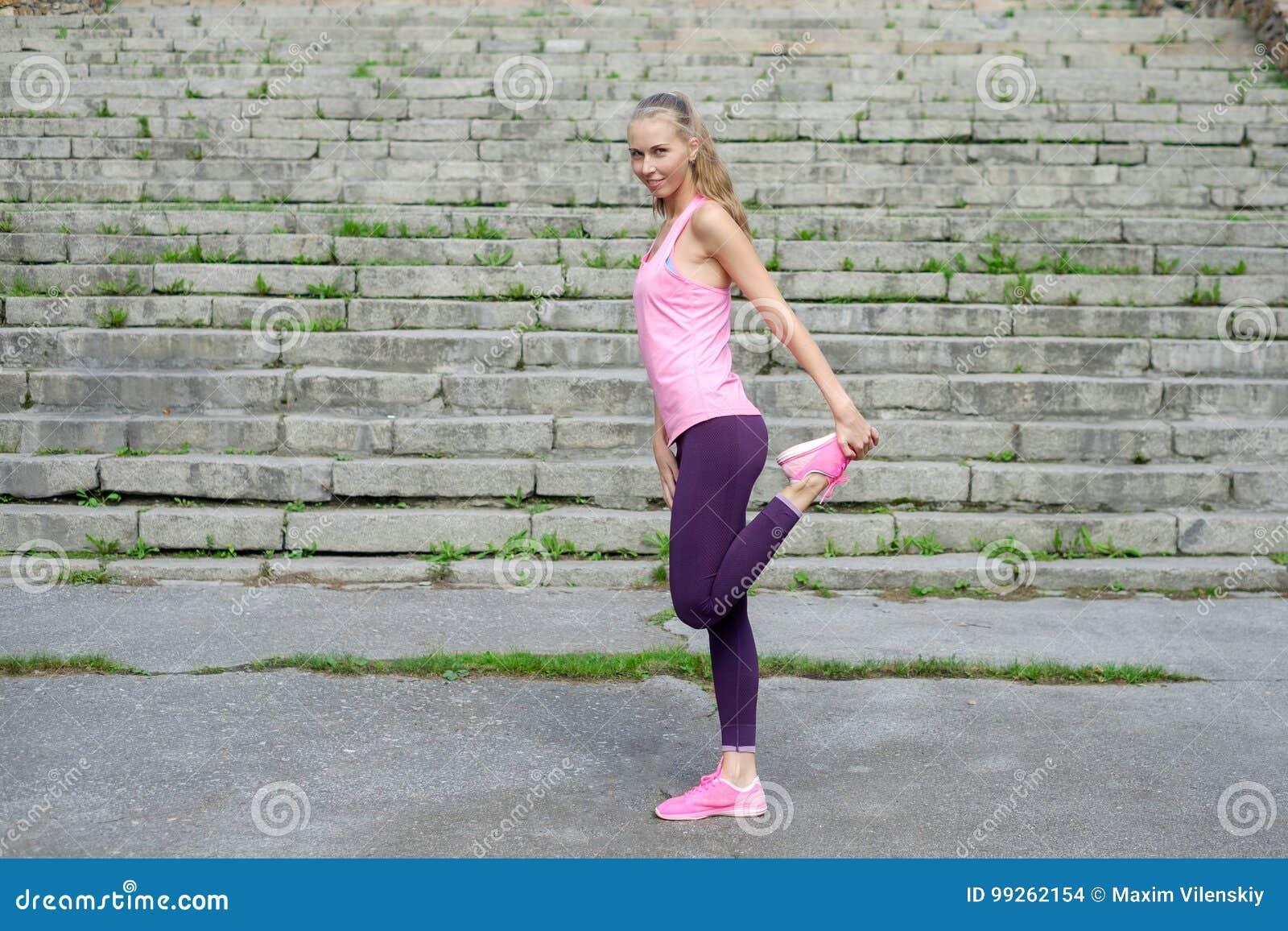 Il ritratto di giovane donna sportiva in vestito da sport fa l allungamento degli esercizi all aperto