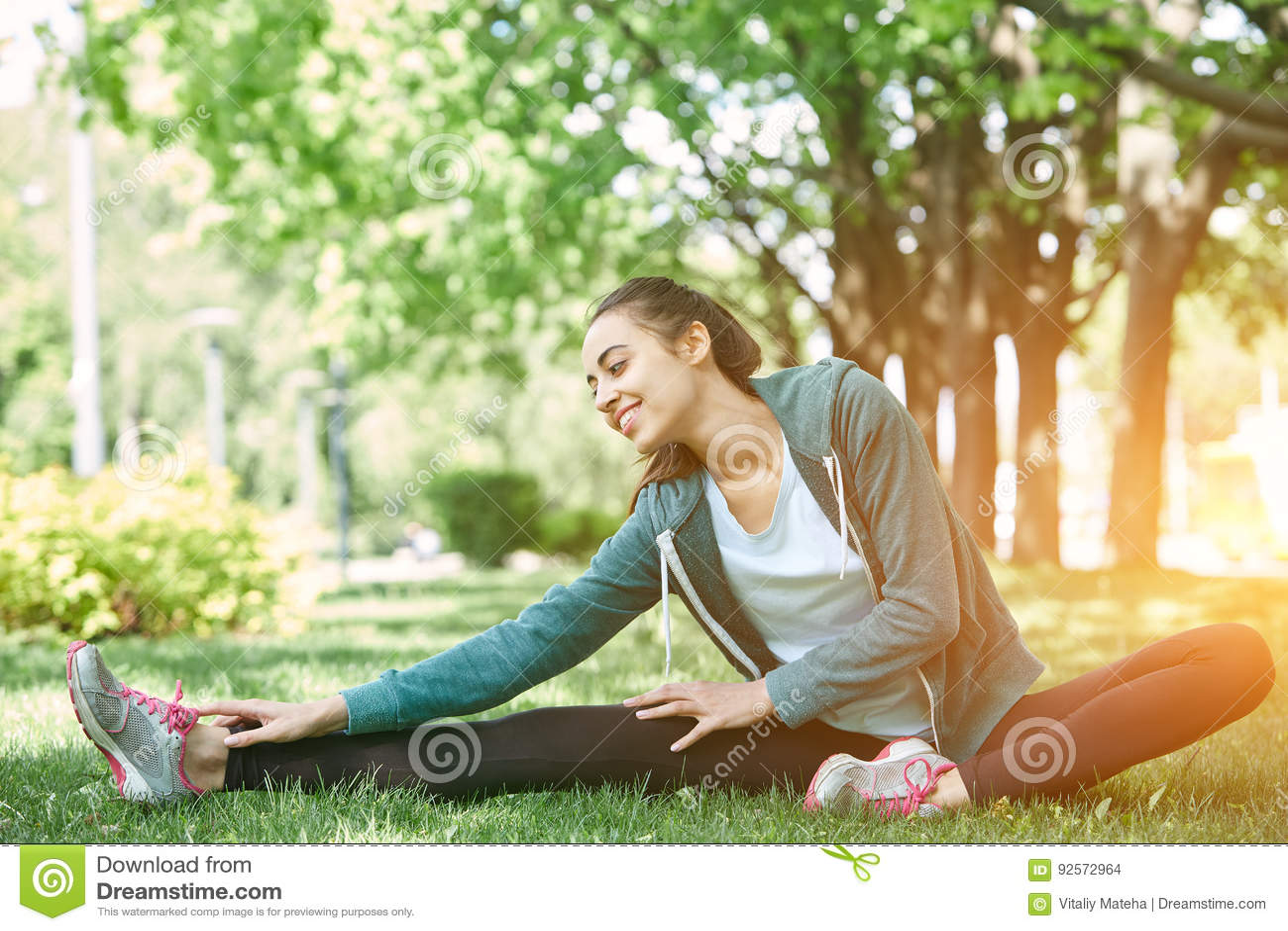 Il ritratto di giovane e donna sportiva in abiti sportivi che fanno l yoga o che allungano si esercita