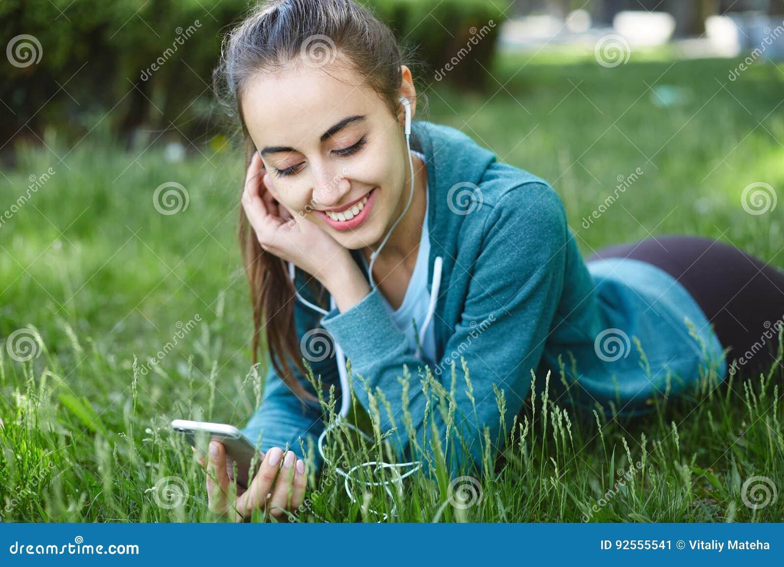 Il ritratto di giovane e donna sportiva in abiti sportivi si trova con lo smartphone sull erba in parco